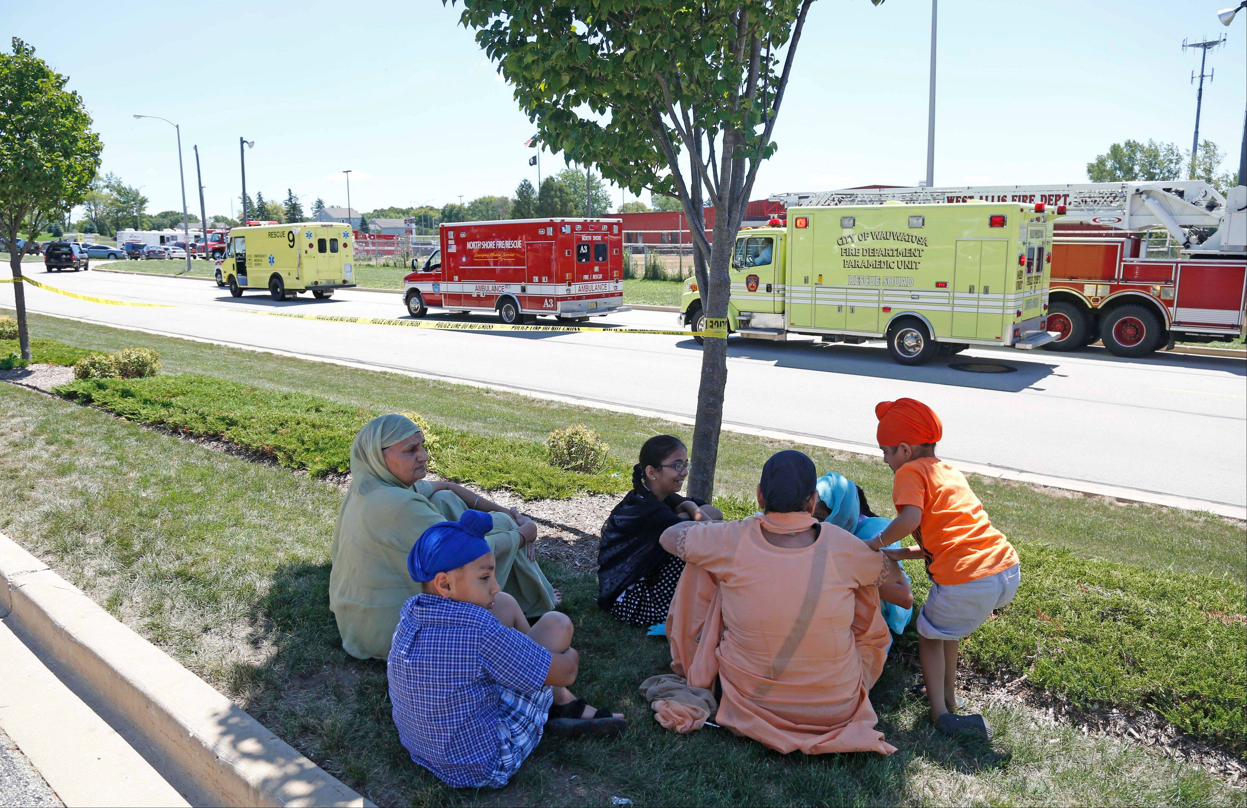 Bystanders sit in the shade at the scene of a shooting inside a Sikh temple in Oak Creek, Wis. Greenfield Police Chief Bradley Wentlandt said tactical officers have been through the temple where shots were fired about 10:30 a.m. Sunday.