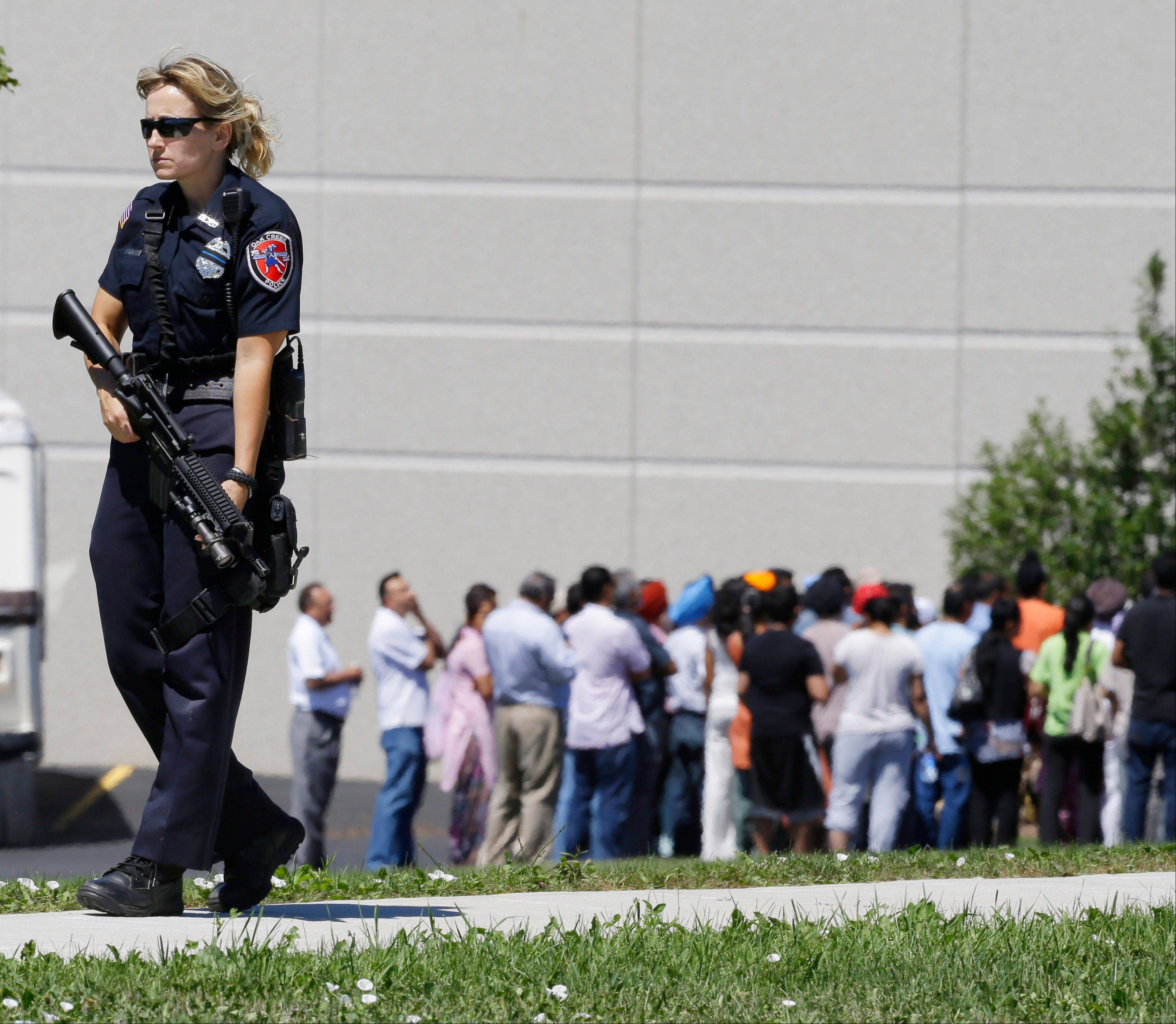 Police stand guard Sunday as bystanders watch at the scene of a shooting inside a Sikh temple in Oak Creek, Wis.