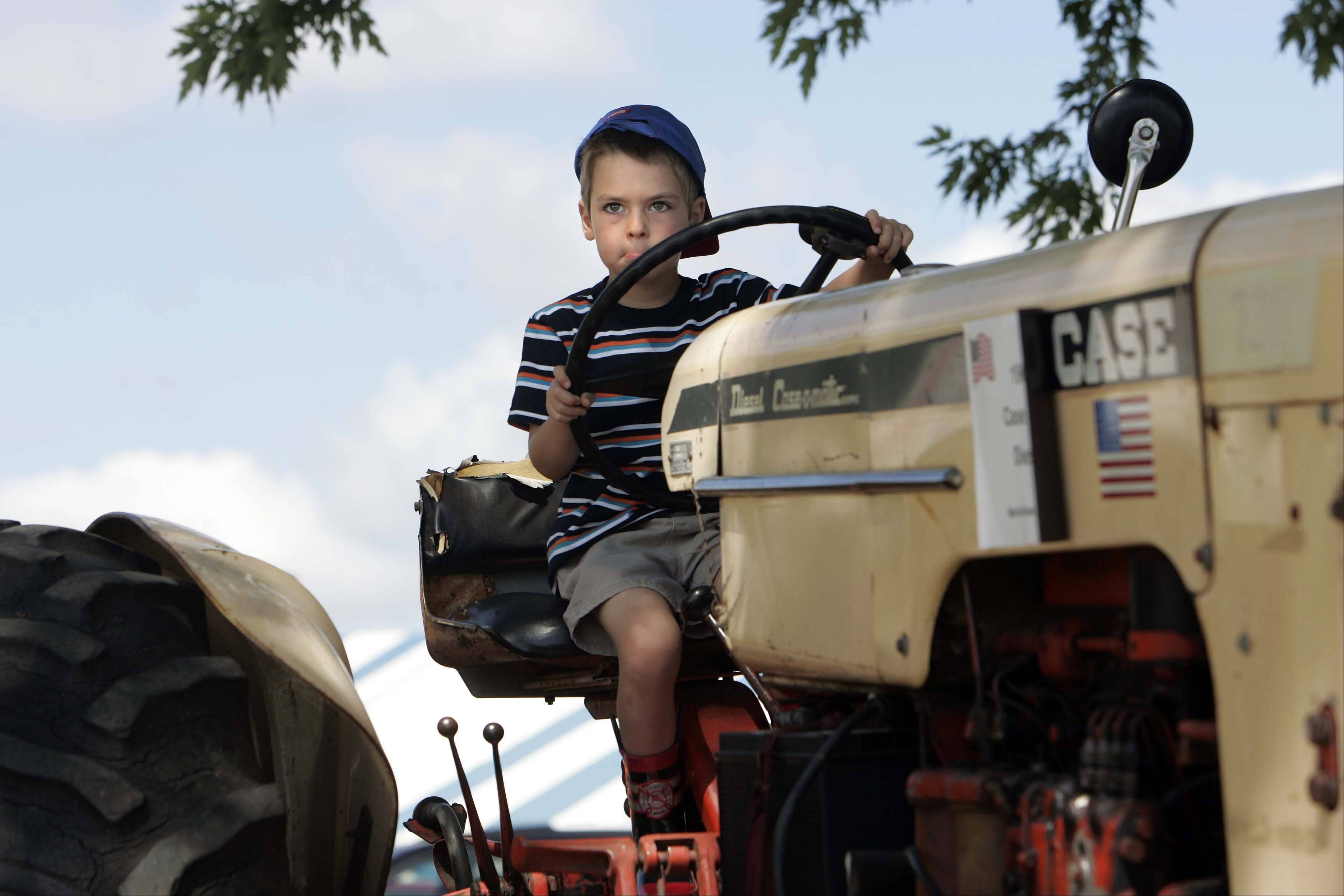 "Skyler McLeer, 4, of Woodstock tries his hand at ""steering"" a 1964 Case 730 Diesel tractor on display at the McHenry County Fair Sunday 2 in Woodstock."