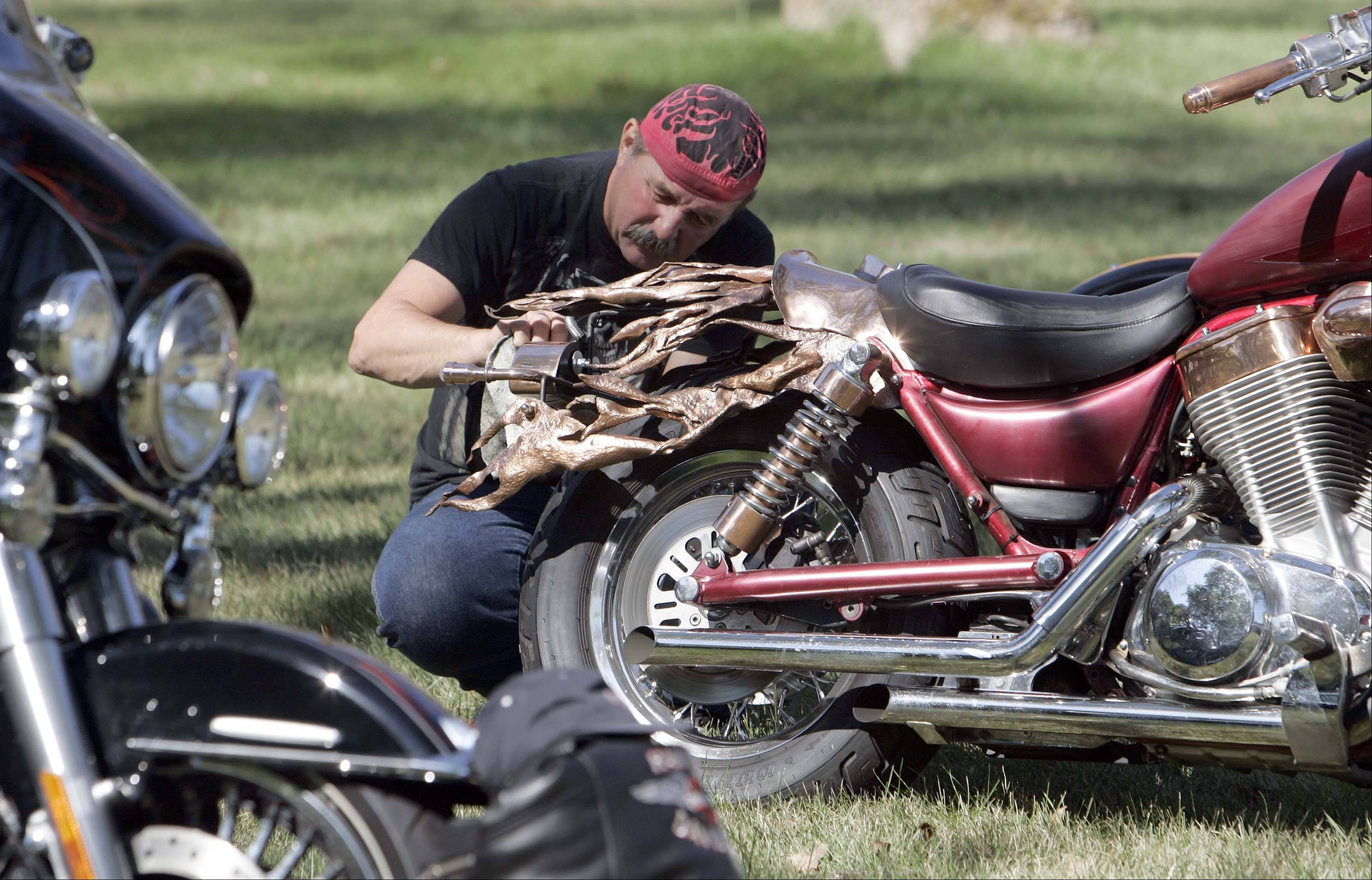Mike Prete of Harvard cleans up his 1998 Suzuki Intruder at the car, truck and bike show during North Aurora Days Sunday at Mooseheart. Prete, a plumber by trade, hand crafted the copper flames on the bike from discarded copper pipe.