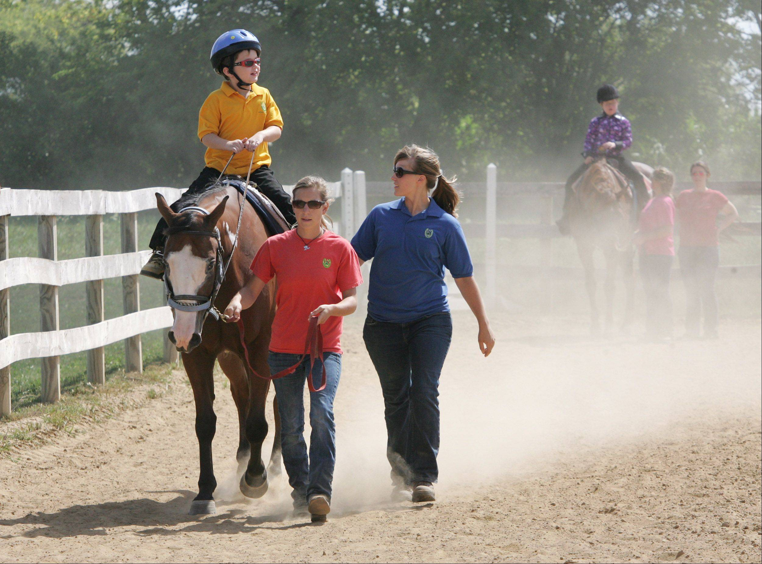 Drew McCarthy, 9, of Antioch, rides Party with help from instructors Lindsey Weick and Marle Novacnik during the Annual Family Summerfest & Participant Horse Show Event Sunday hosted by Partners For Progress at their new Premier Equine Therapy Center in Wauconda. The program's riders with special needs showcased their riding skills for family and friends.