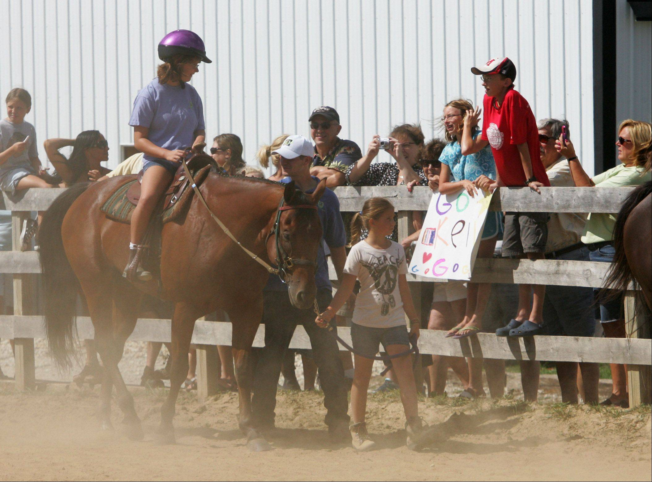 Kelly Corbin, 12, of Hawthorn Woods, rides Duncan as she hears cheers from family members during the Annual Family Summerfest & Participant Horse Show Event hosted by Partners For Progress Sunday at the Premier Equine Therapy Center in Wauconda.