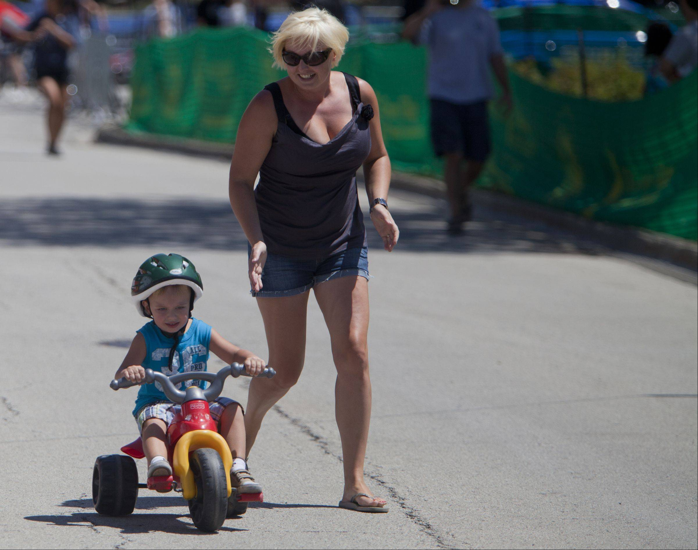 Agnirszka Sosinska runs next to her son Nathan, 4, during the Shamino Big Wheels event during the third day of the Tour of Elk Grove.