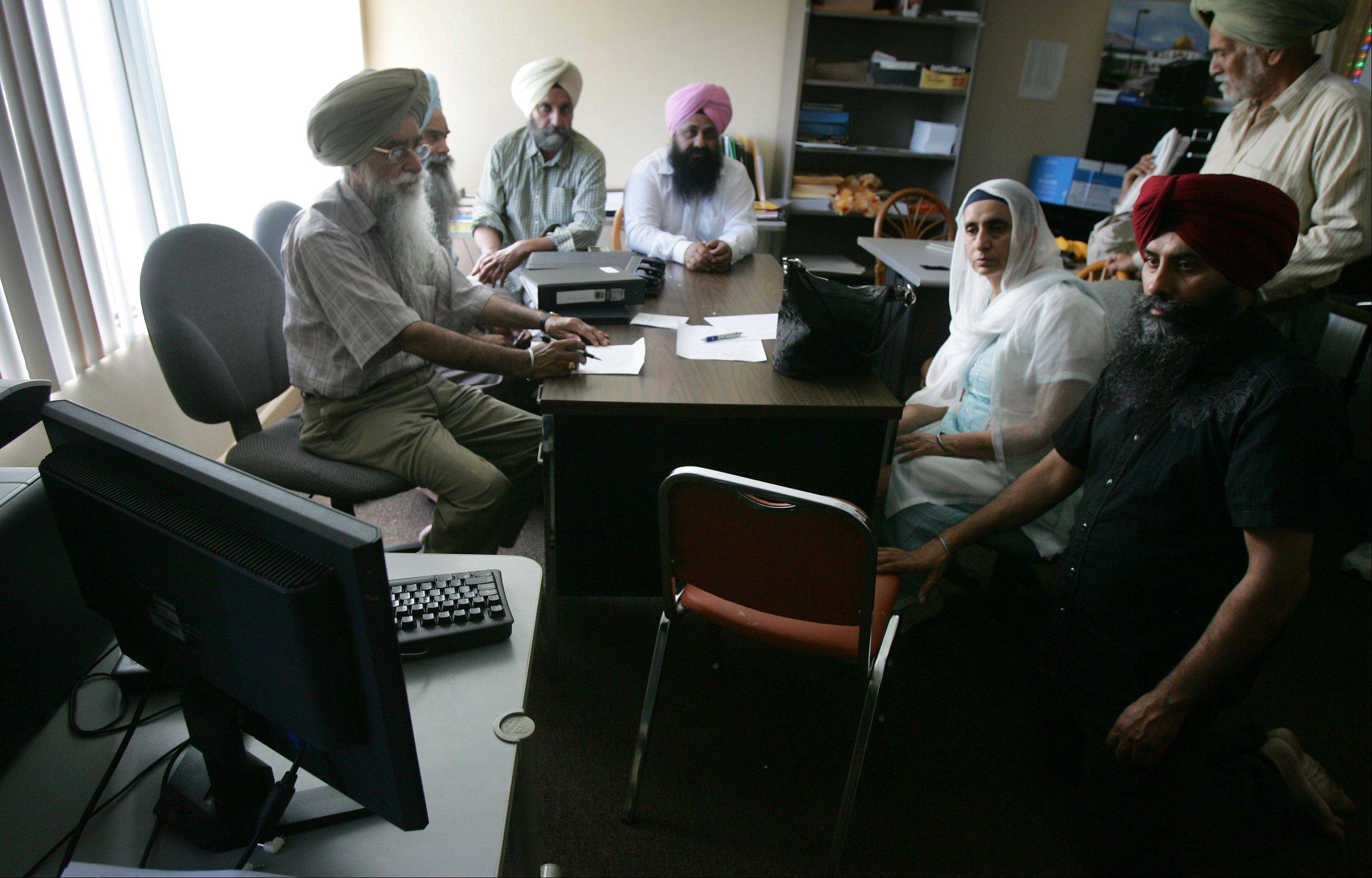 Members of the Gurudawara Sikh Religious Society in Palatine sit in an office as they watch the news Sunday of the shooting at a Sikh temple near Milwaukee.