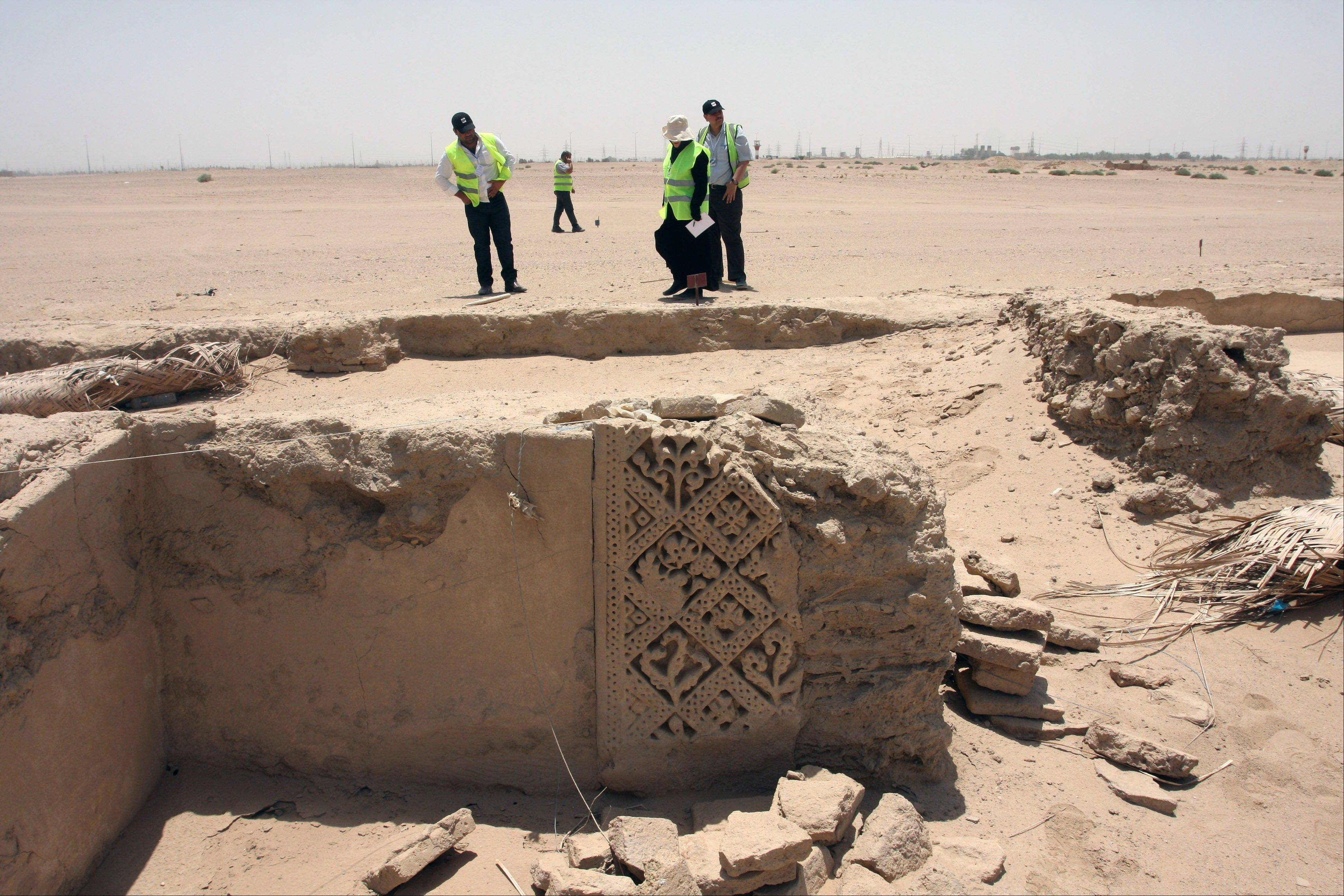 Archaeologists on July 10 stand next to ruins that scholars think may be from the legendary Arab Christian city of Hira.