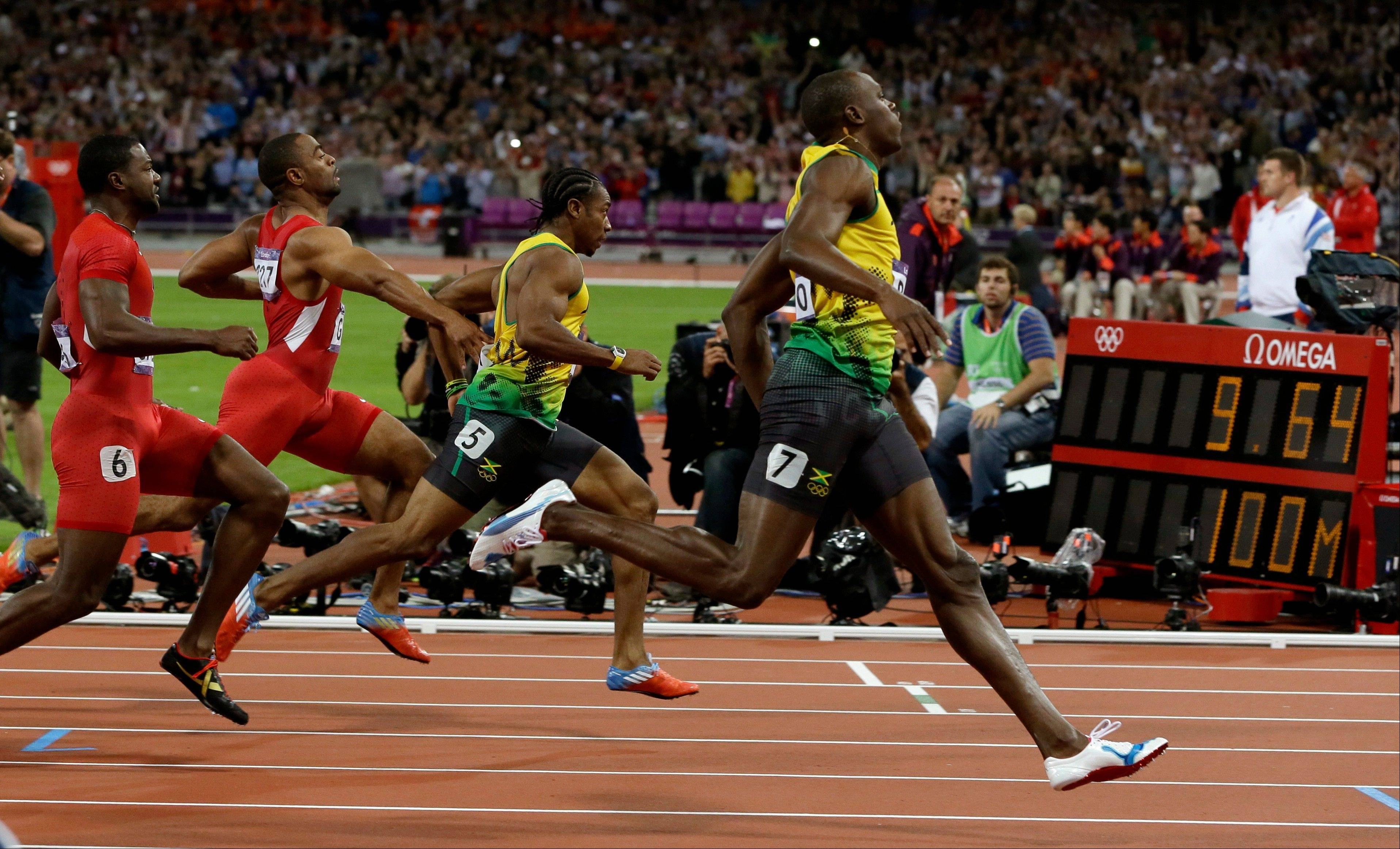 Jamaica's Usain Bolt, right, wins the men's 100-meter final Sunday at Olympic Stadium in London.