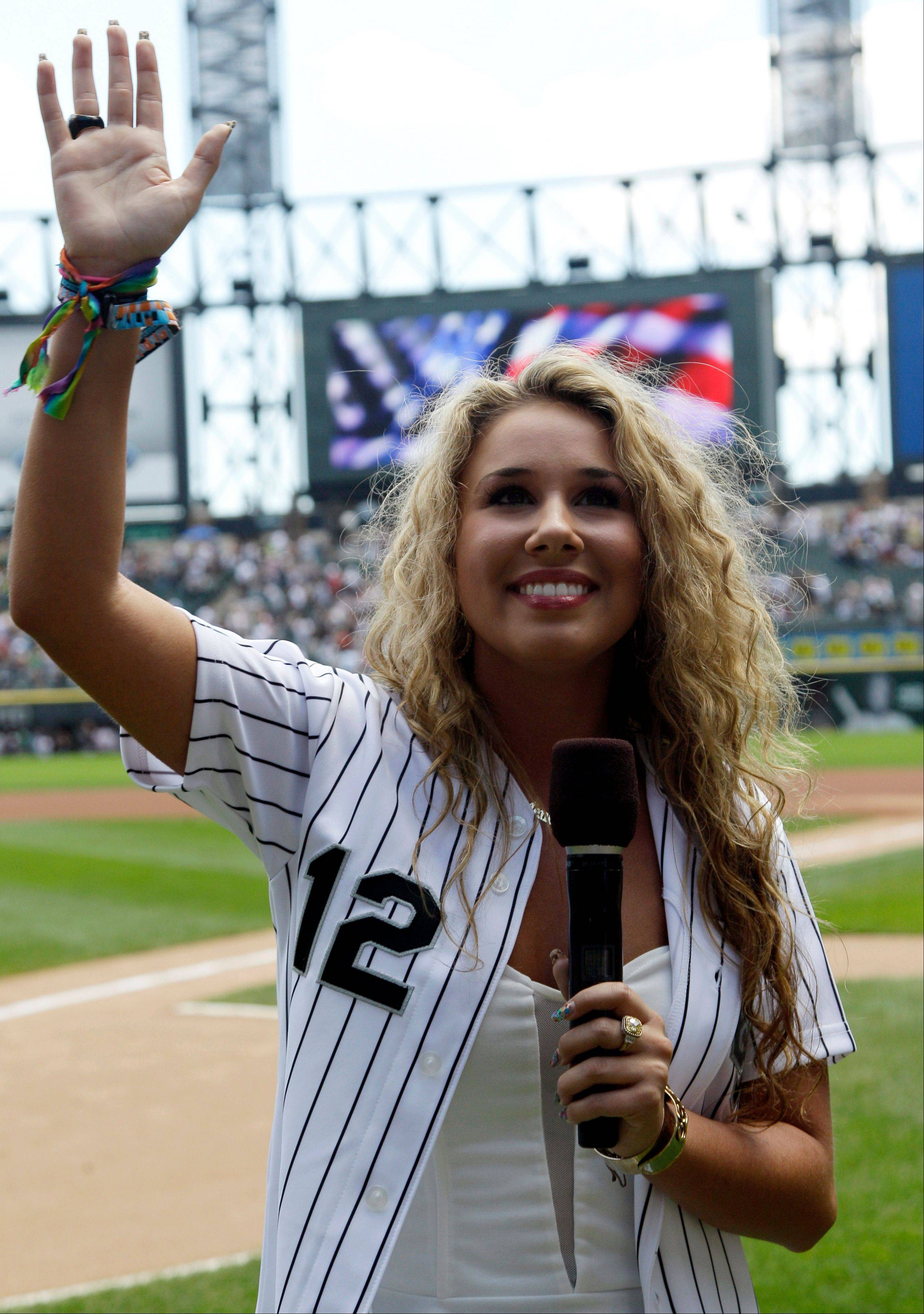 Singer-songwriter and Wheeling native Haley Reinhart waves to fans before singing the national anthem Sunday at U.S. Cellular Field.