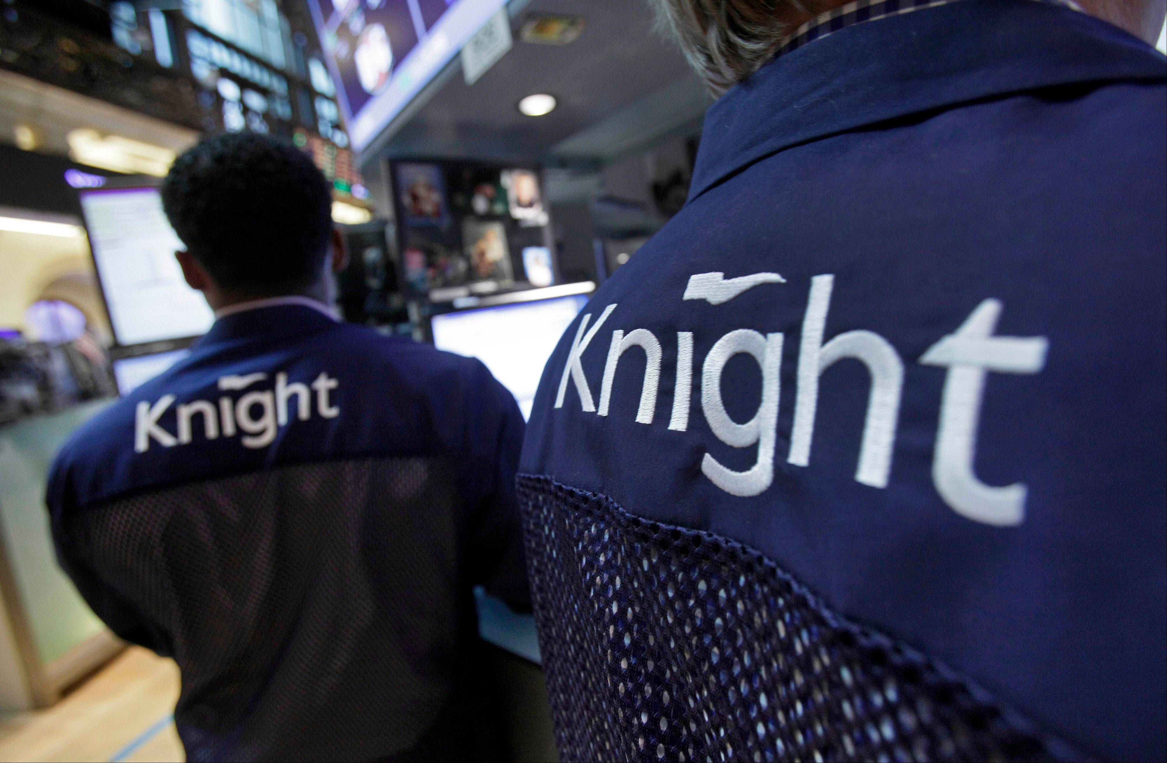 Knight Capital specialists work at their posts on the floor of the New York Stock Exchange. Knight Capital announced Monday that investors have agreed to supply it with $400 million in financing, which would help the trading firm stay in business after last week's disastrous software glitch that shook U.S. stock trading and jeopardized its future.