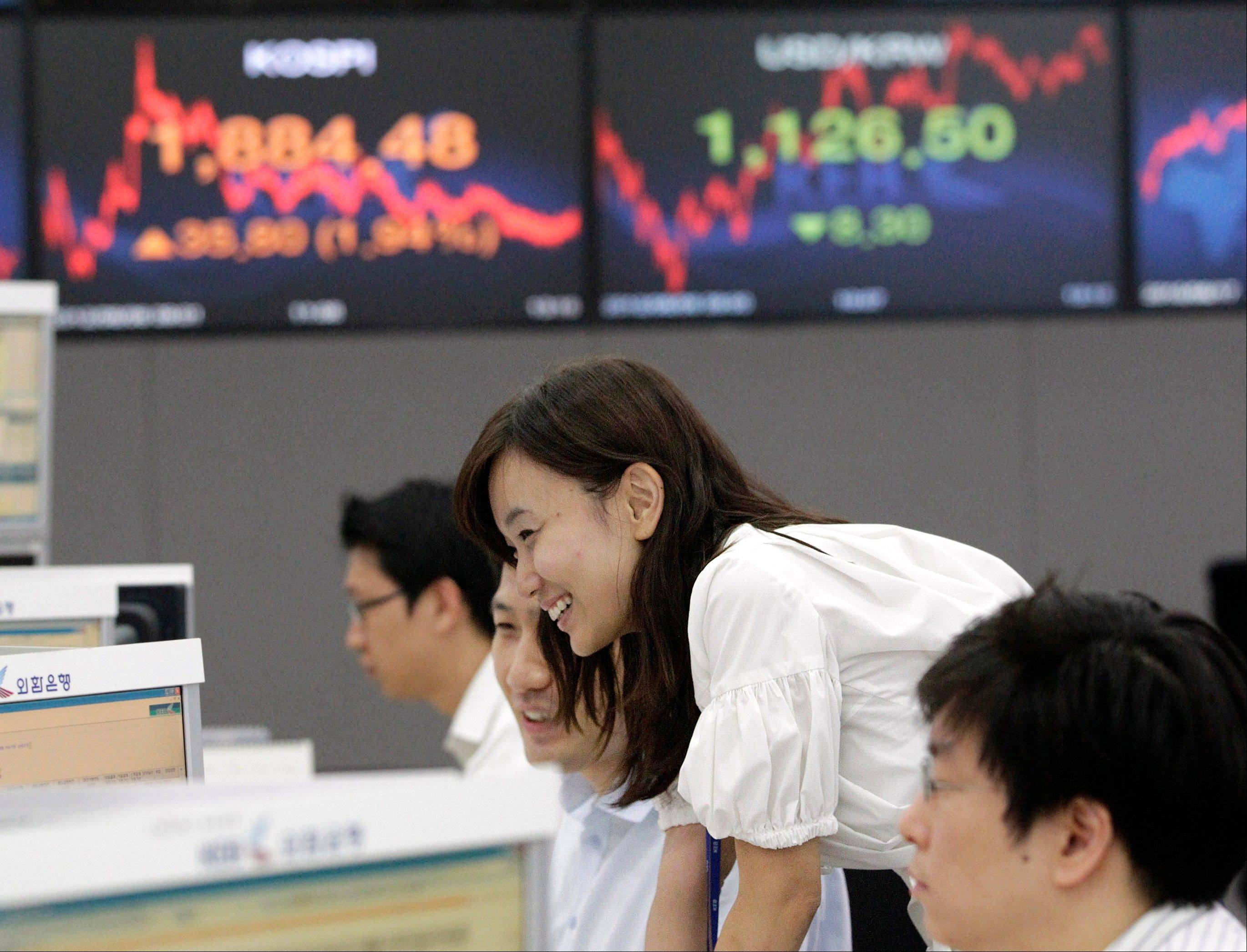 Currency traders smile at the foreign exchange dealing room of the Korea Exchange Bank headquarters in Seoul, South Korea, Monday.