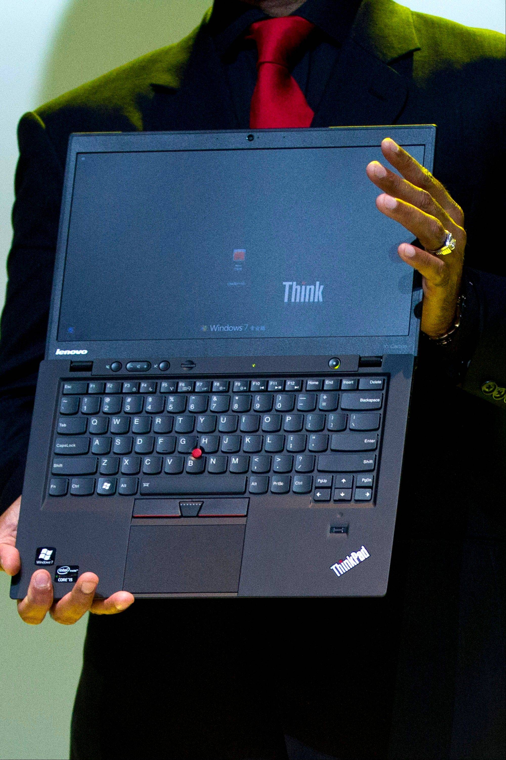 Lenovo Vice President Dilip Bhatia holds a new ThinkPad X1 Carbon laptop in Beijing Monday