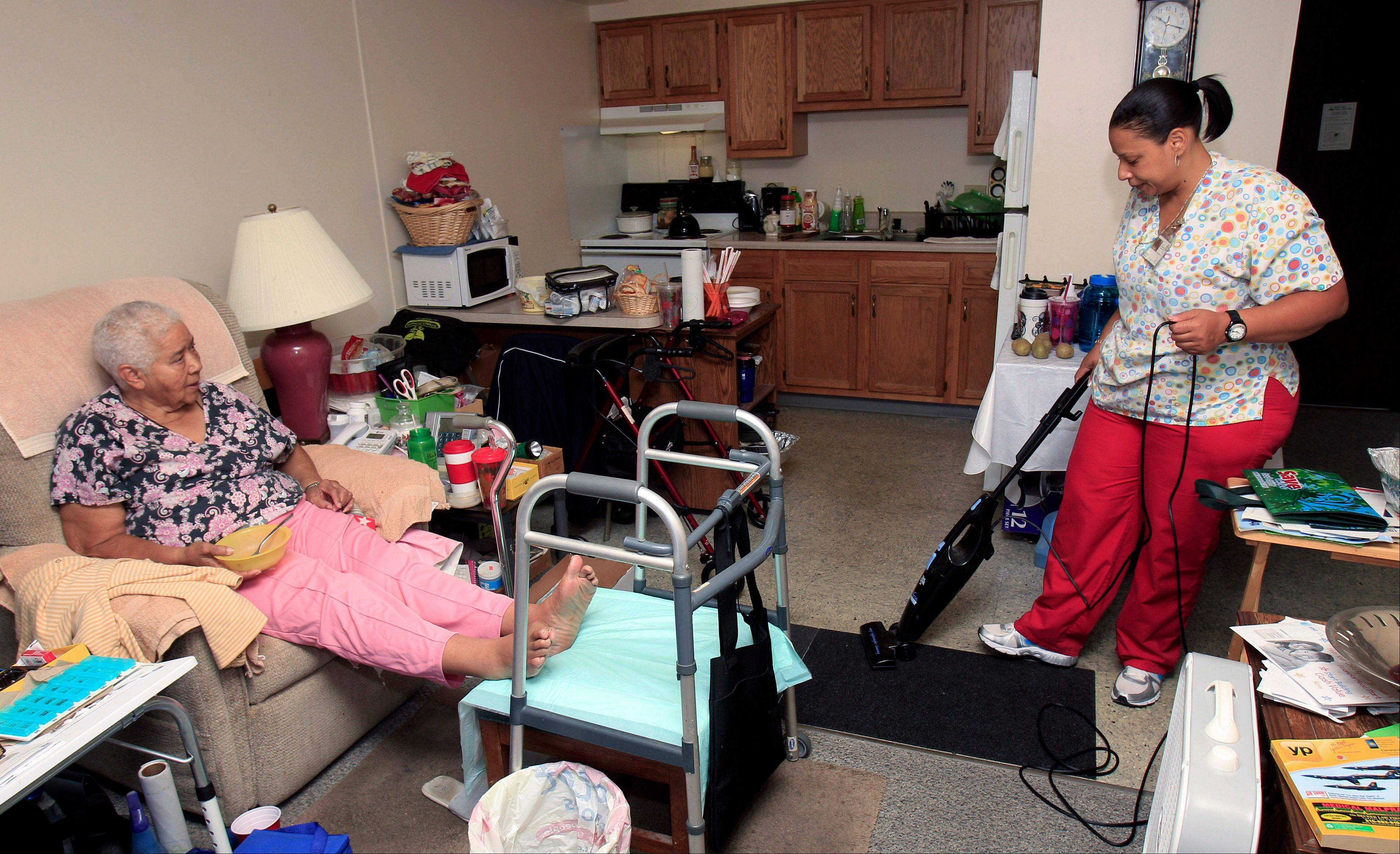 Taura Tate, right, a home care aide since 1999, vacuums as Crell Johnson, 76, looks on at Johnson's apartment in Euclid, Ohio.