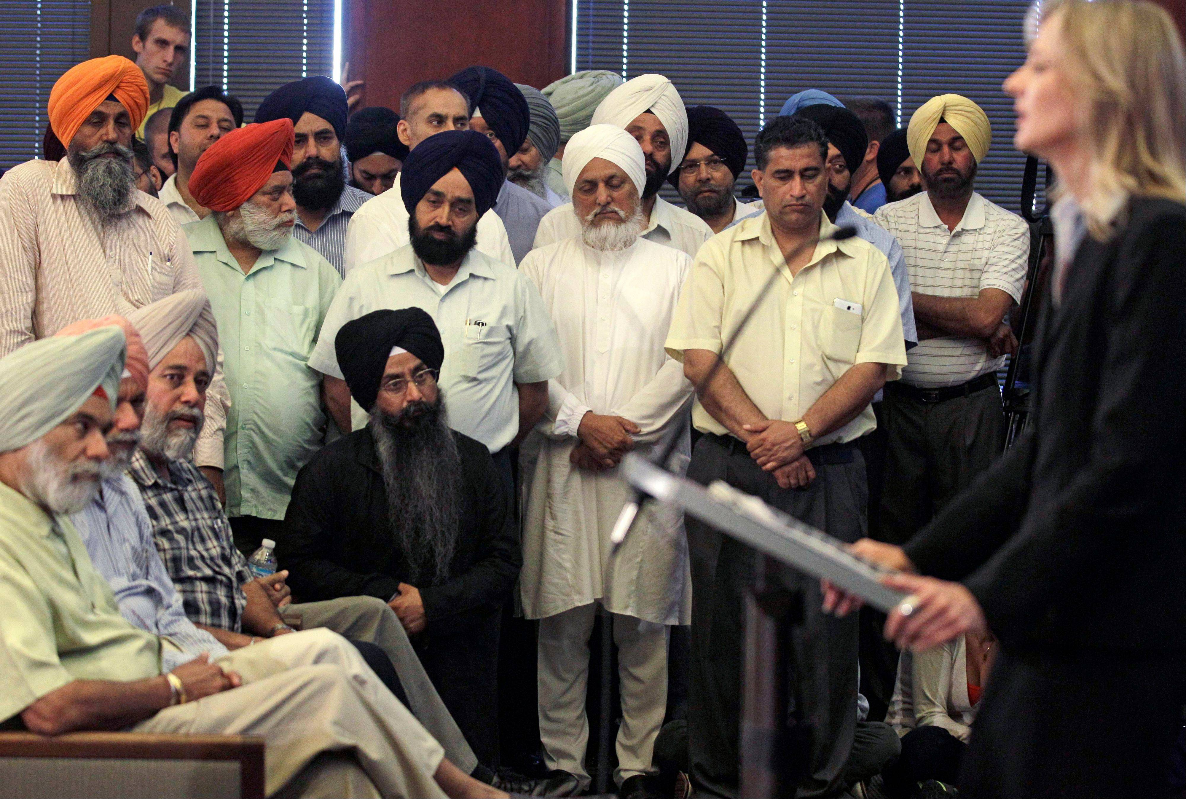 Members of the Sikh Temple of Wisconsin listen to FBI Special Agent in Charge, Teresa Carlson, during a news conference in a municipal building in Oak Creek, Wis., Monday.