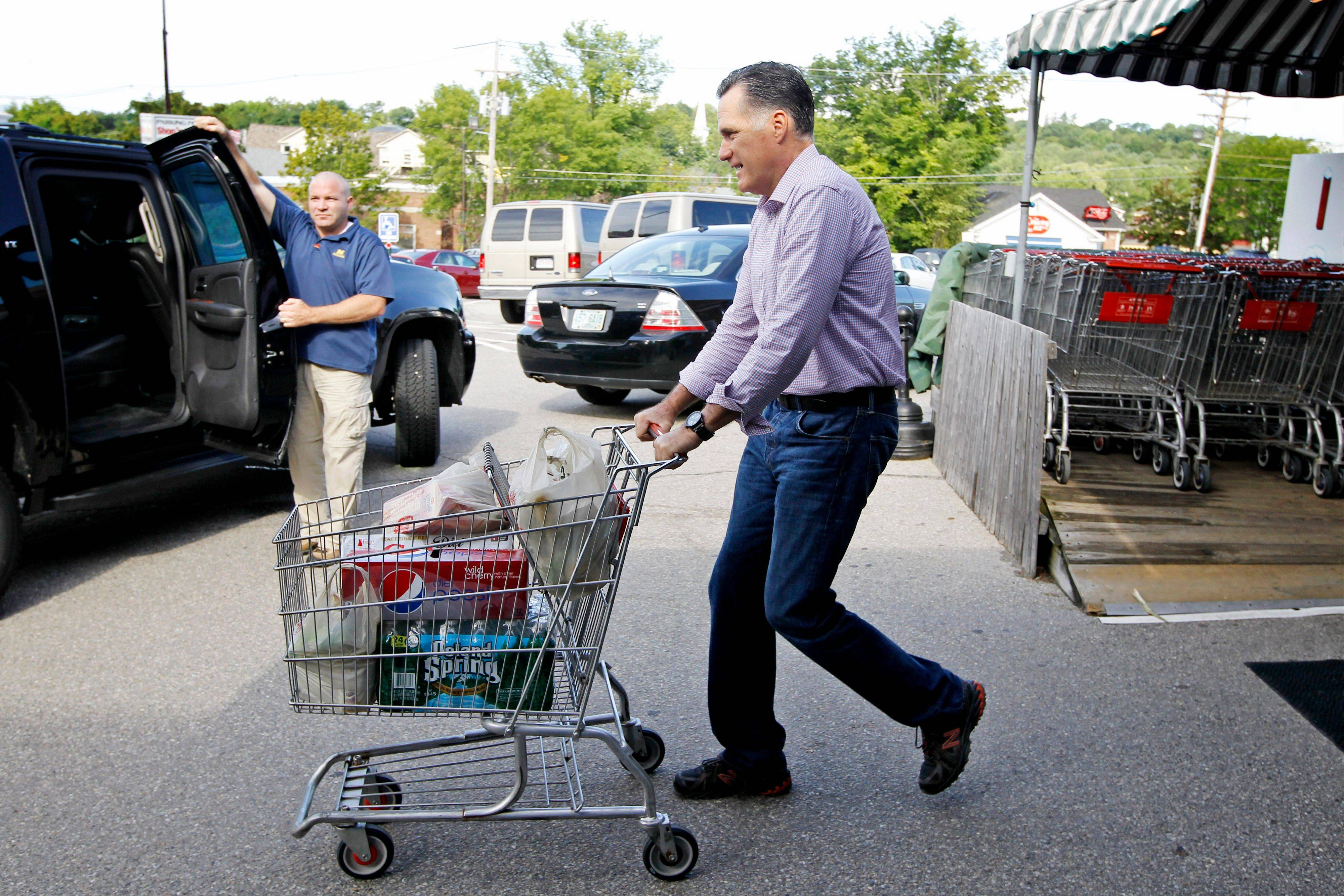 Republican presidential candidate, former Massachusetts Gov. Mitt Romney pushes a shopping cart after buying groceries at Hunter's Shop and Save supermarket in Wolfeboro, N.H., Monday.