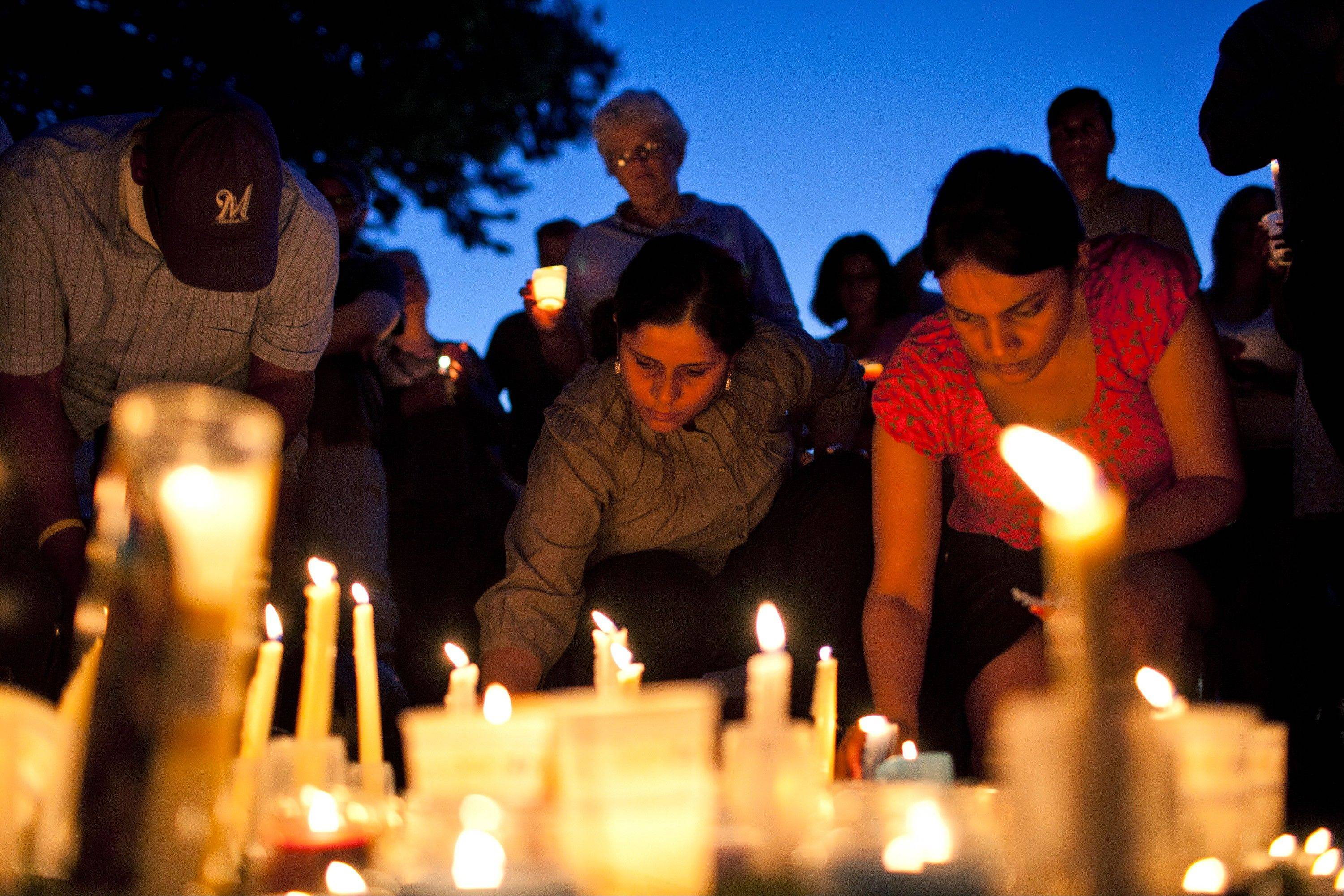 Mourners gather at a candlelight vigil for the victims of the Sikh Temple of Wisconsin shooting Sunday at Cathedral Square in Milwaukee. A gunman killed six people at the suburban Milwaukee temple on Sunday in a rampage that left terrified congregants hiding in closets and others texting friends outside for help.