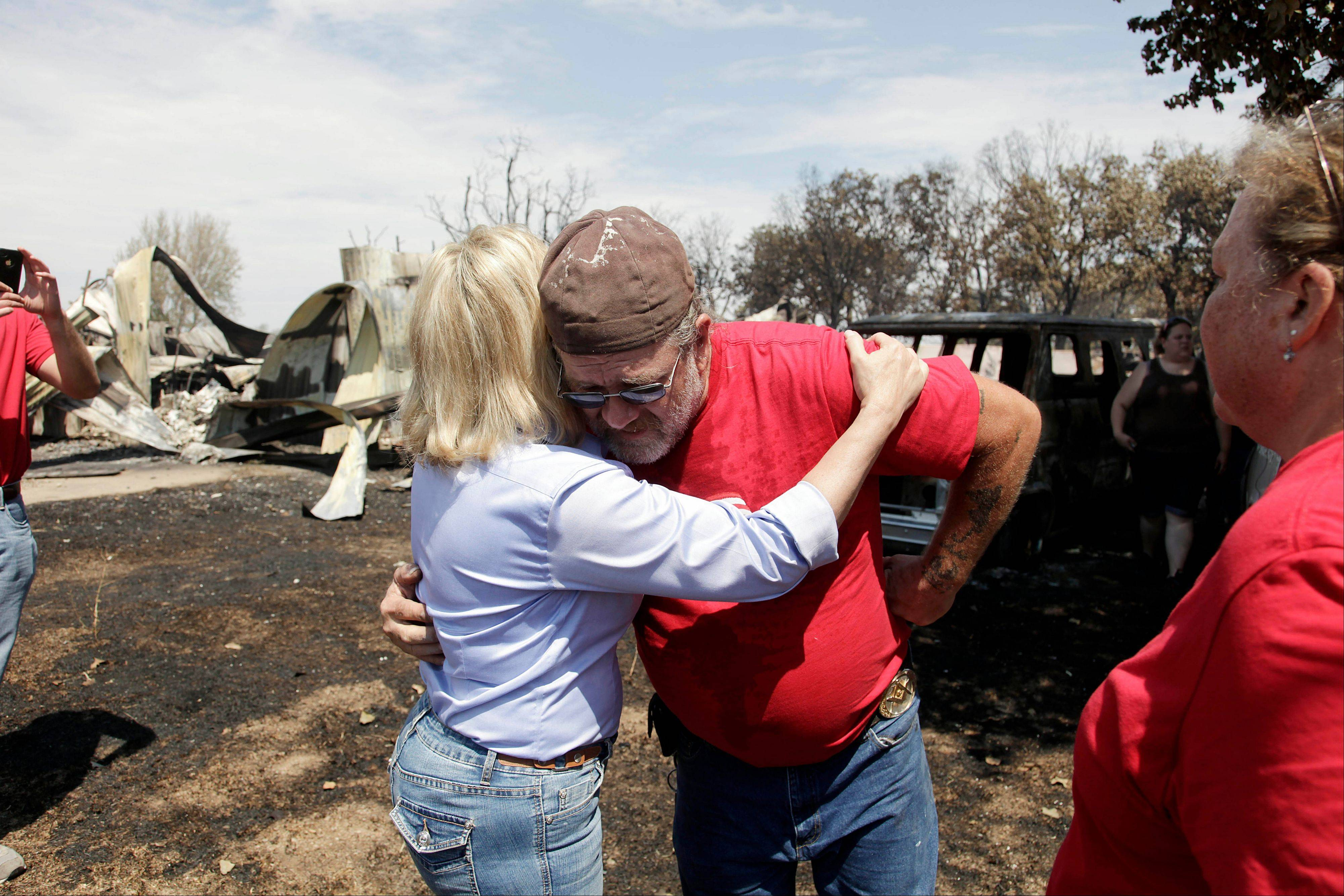 Gov. Mary Fallin, left, hugs James Sparr who lost his home and business, in the background, after wildfires burned across the state in Mannford, Okla., Sunday.