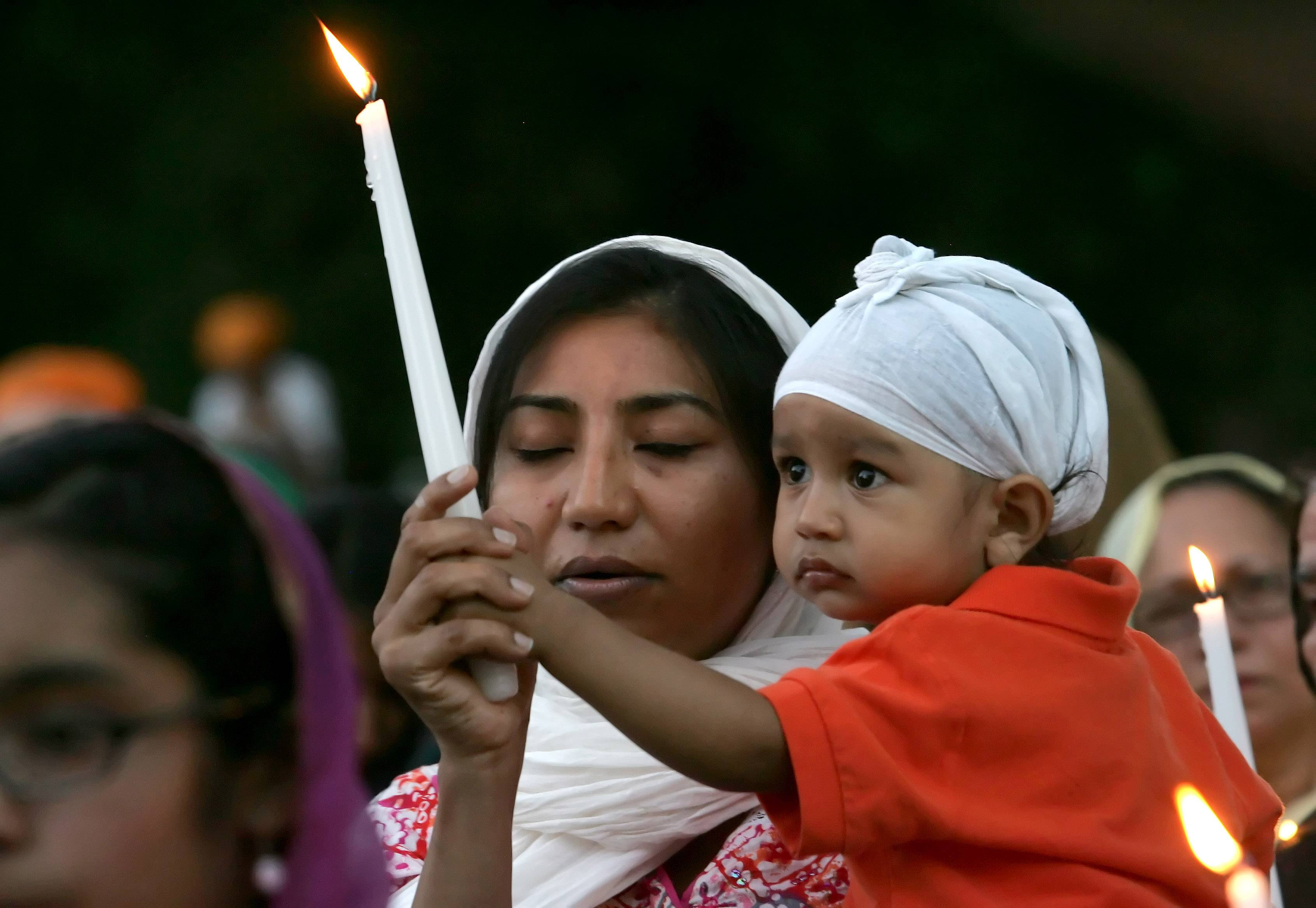 Kawal Preet and her son Prabhnek, 15 months, visiting from San Francisco, take part in the candlelight vigil at Illinois Sikh Community Center in Wheaton on Monday.