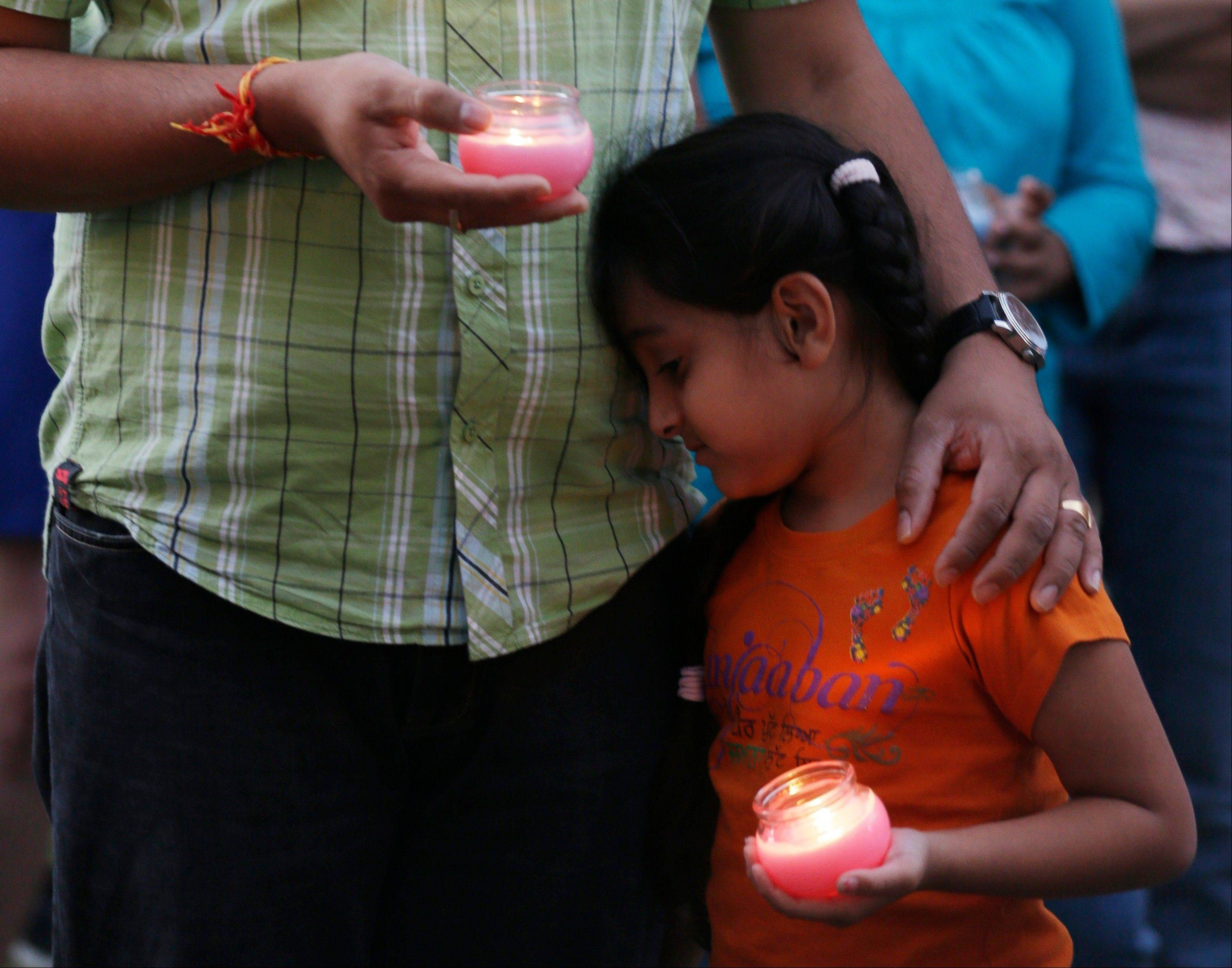 A man holds his child during a candle light vigil for the victims of the Sikh Temple of Wisconsin shooting in Milwaukee Sunday.