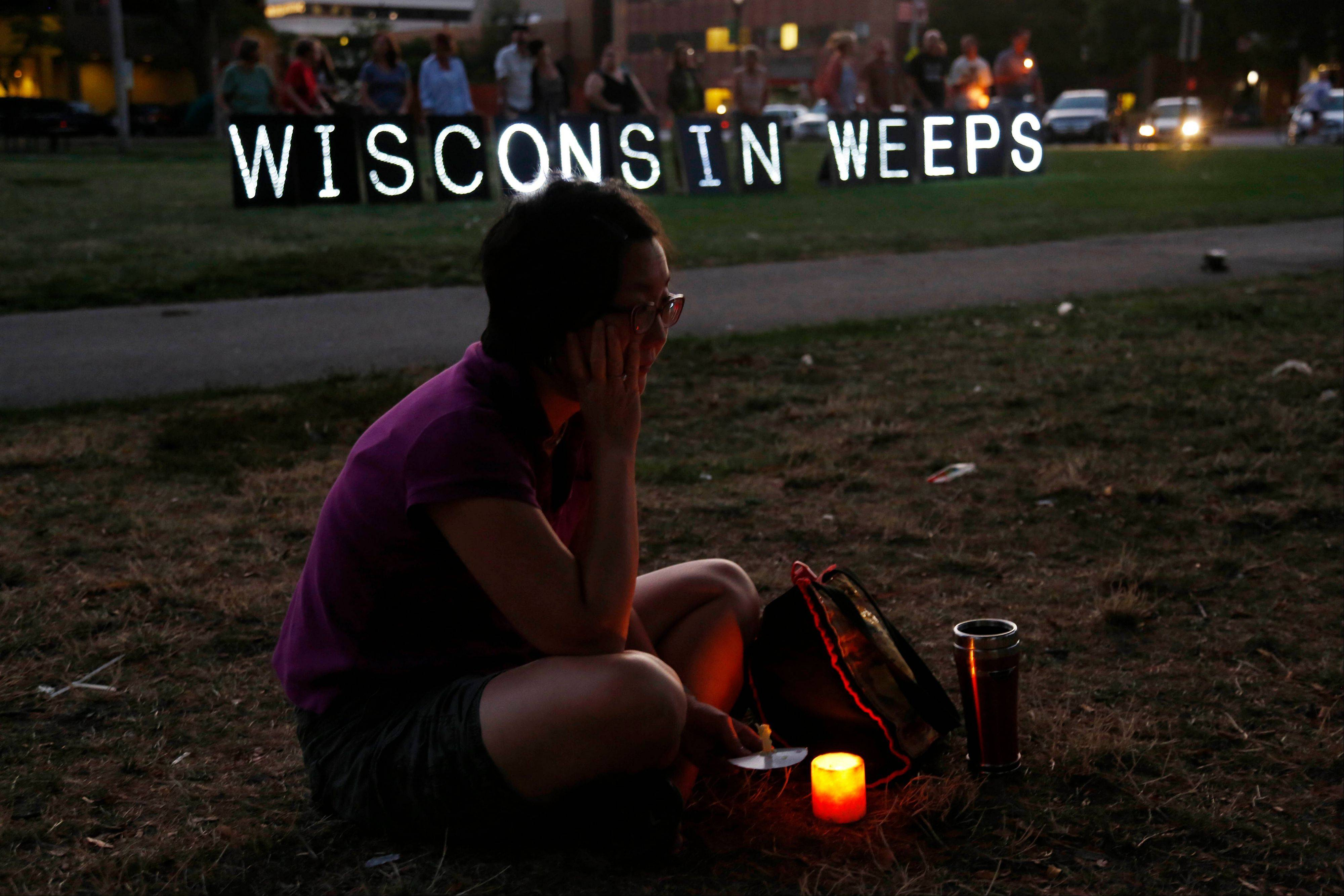 A woman sits with a candle during a vigil Sunday for the victims of the Sikh Temple of Wisconsin shooting in Milwaukee.