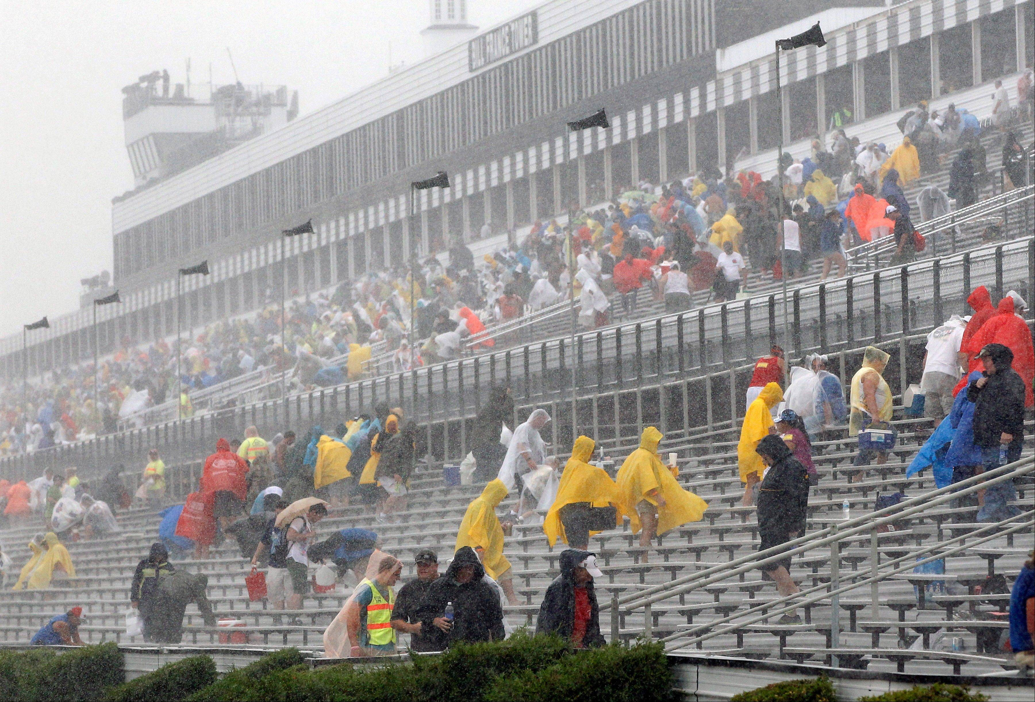 Fans leave the stands after the start of the NASCAR Sprint Cup Series auto race was postponed due to lightning and heavy rain on Sunday at Pocono Raceway in Long Pond, Pa.