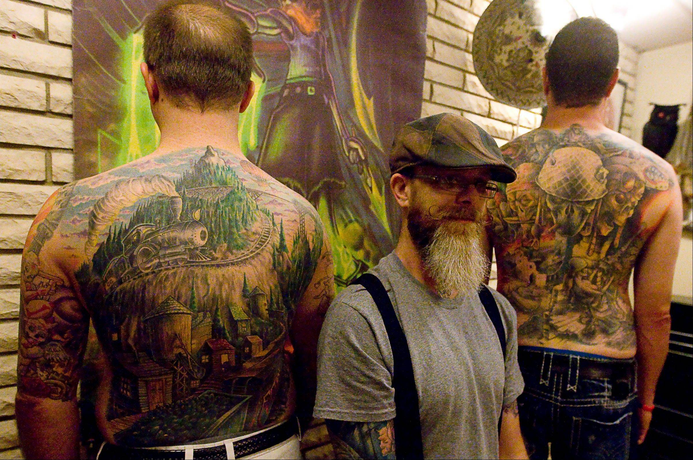Jason Campbell, center, a Decatur native, sits with two award winning models of his work as a tattoo artist in his Springfield.