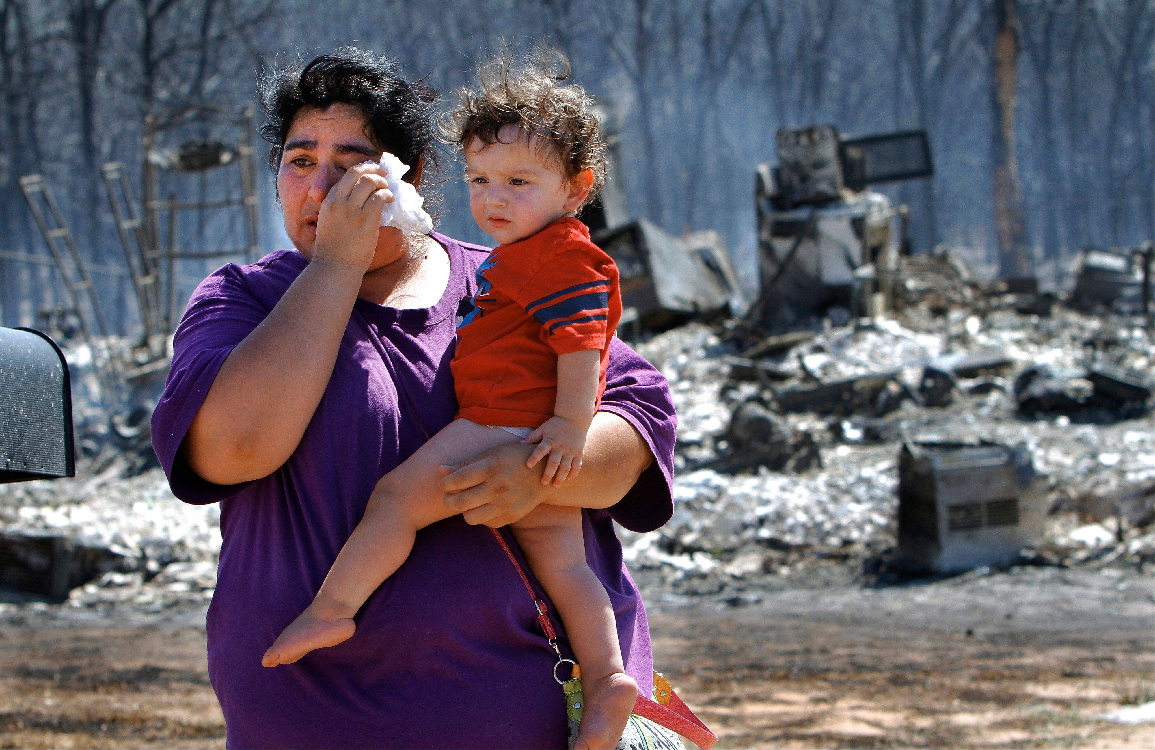 Victoria Landavazo holds youngest child, Axel, 1, while wiping tears after seeing what the wildfire in Luther, Okla., had done to their home there. The fire near Luther, which is about 25 miles northeast of Oklahoma City, destroyed nearly five dozen homes and other buildings before firefighters were able to gain some measure of control Saturday.