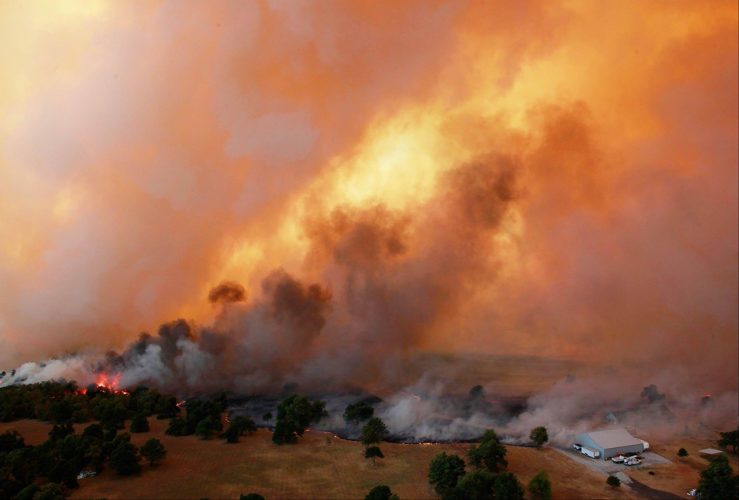 Flames burn near Highway 48 and HW 38 junction east of Drumright, Okla., on Saturday. Emergency management officials have ordered evacuations of homes in several areas as wildfires burn across the state.