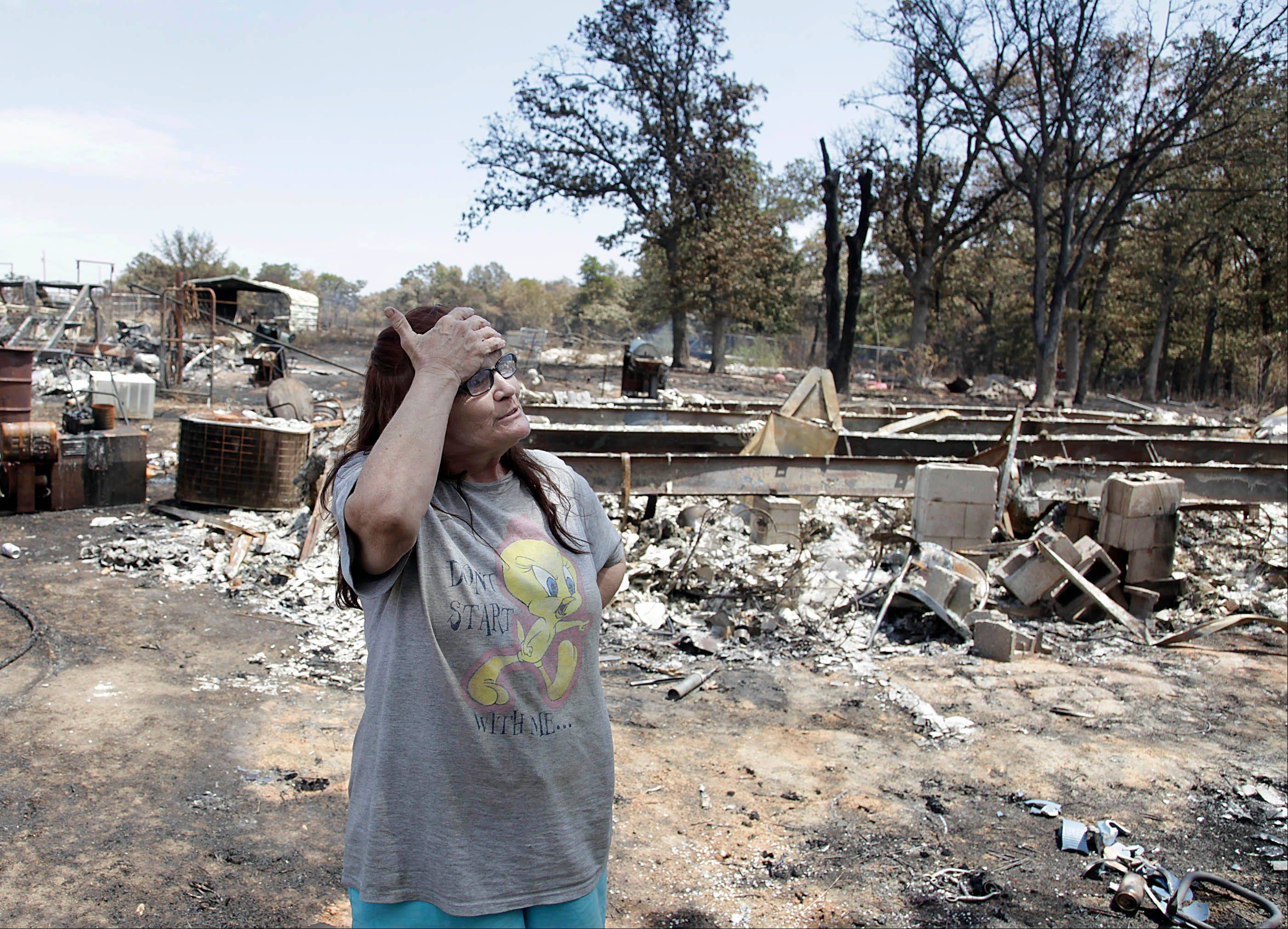 Sandra Jordan reacts as she speaks about the remains of her home (in the background) that was destroyed by a wildfire in Mannford, Okla., Sunday.