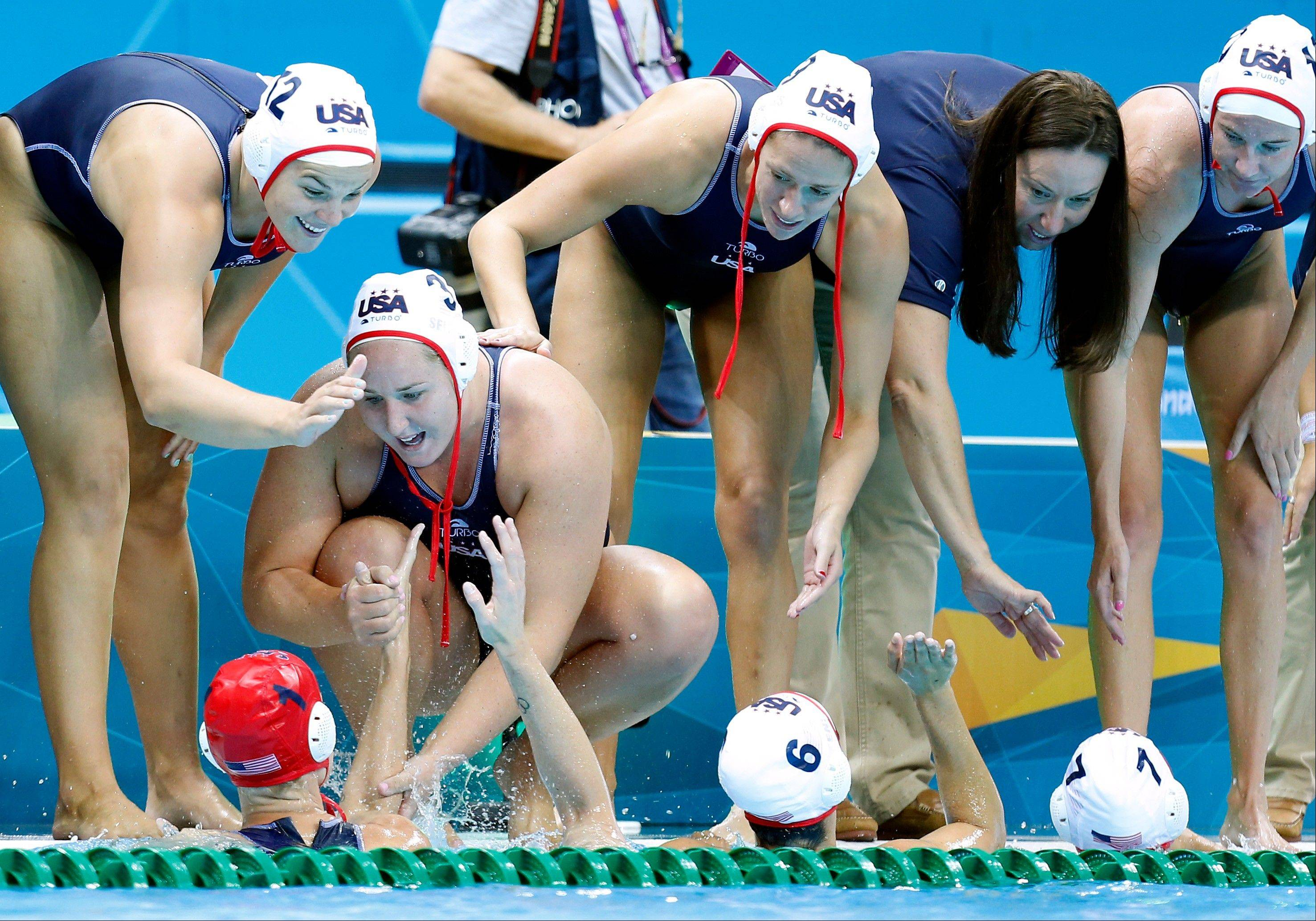 Kami Craig, left and Melissa Seidemann, second left, reaches down to shake hands with goalkeeper Betsey Armstrong all of the United States water polo team after they defeated Italy in their women's water polo quarterfinal match at the 2012 Summer Olympics, Sunday, Aug. 5, 2012, in London.