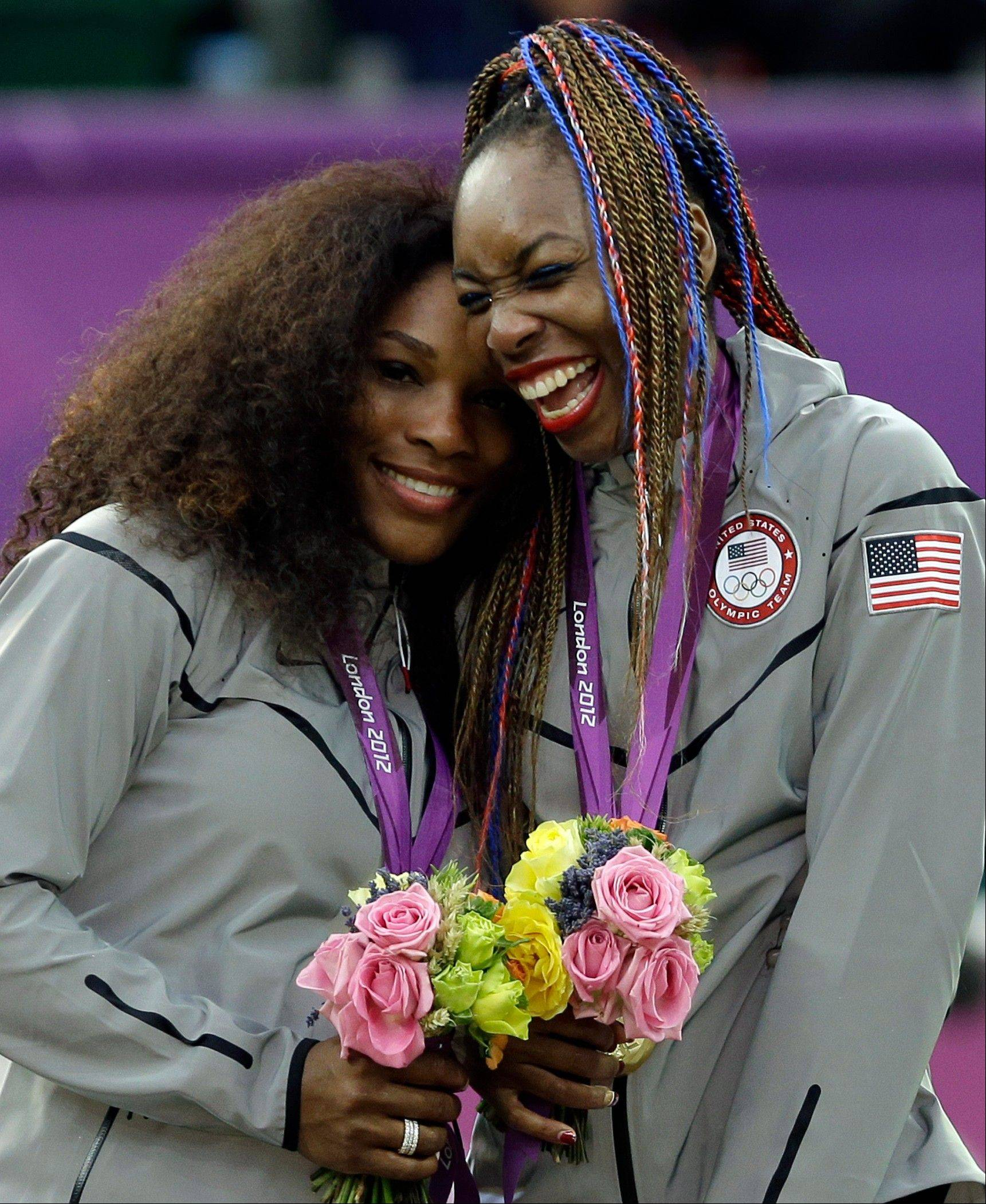 Serena Williams, left, and Venus Williams of the United States laugh together on the podium after receiving their gold medals in women's doubles at the All England Lawn Tennis Club in Wimbledon, London at the 2012 Summer Olympics, Sunday, Aug. 5, 2012.