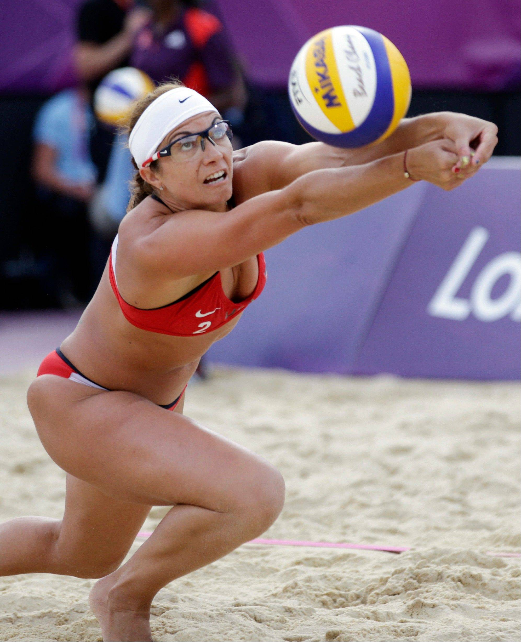 Misty May Treanor of the United States returns a ball during a beach volleyball match against Italy at the 2012 Summer Olympics, Sunday, Aug. 5, 2012, in London.