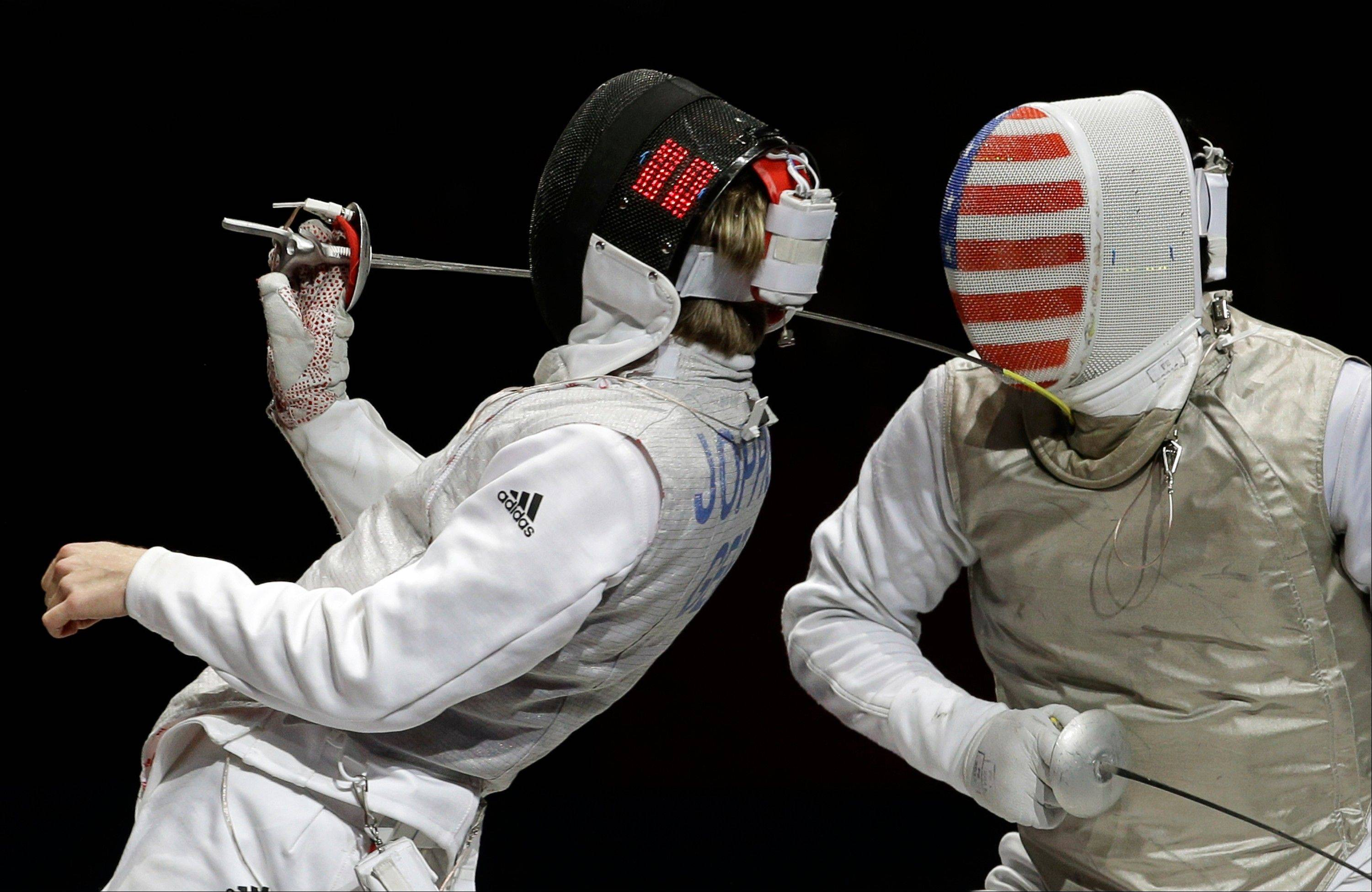 Peter Joppich of Germany competes against Gerek Meinhardt of the United States, right, during the men's foil team fencing competition at the 2012 Summer Olympics, Sunday, Aug. 5, 2012, in London.