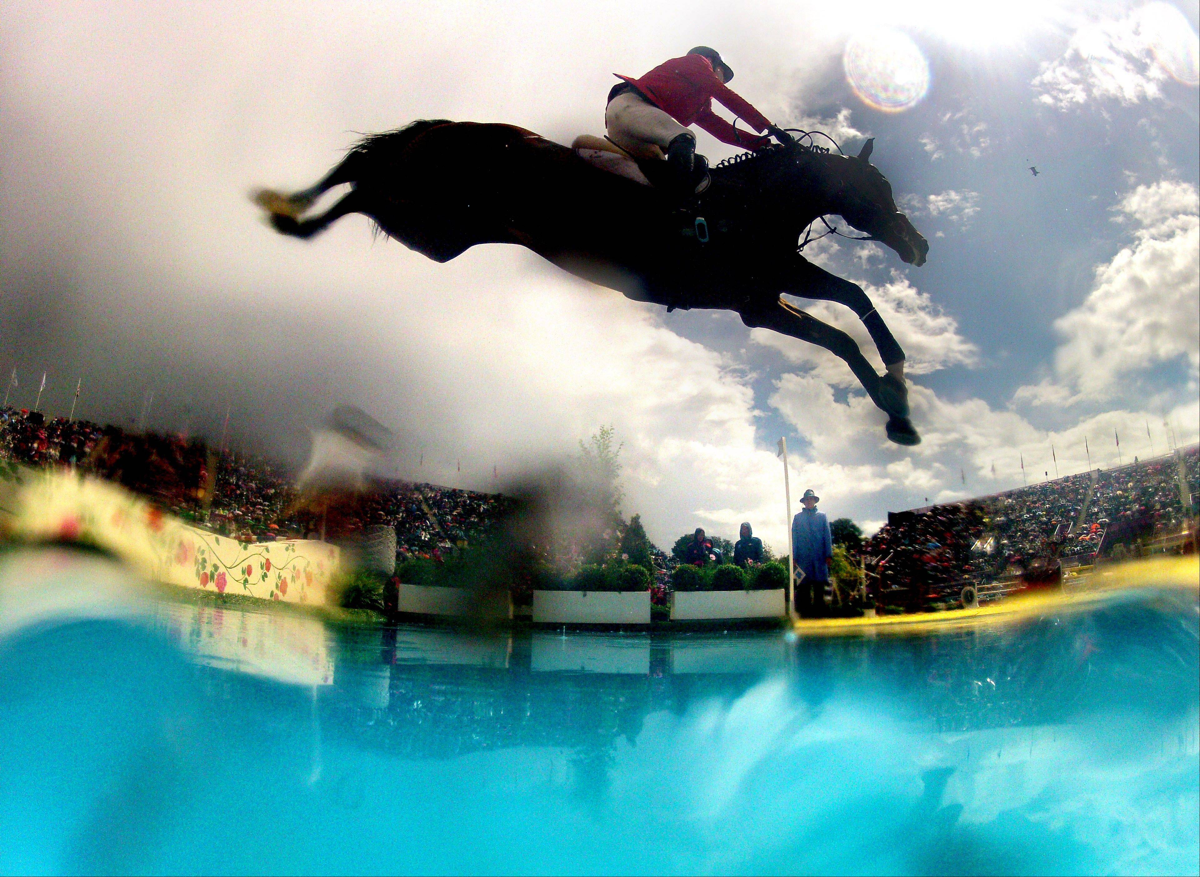 In this photo made using a fisheye lens, Jaime Azcarraga, of Mexico, rides his horse Gangster, in the equestrian show jumping team competition at the 2012 Summer Olympics, Sunday, Aug. 5, 2012, in London.