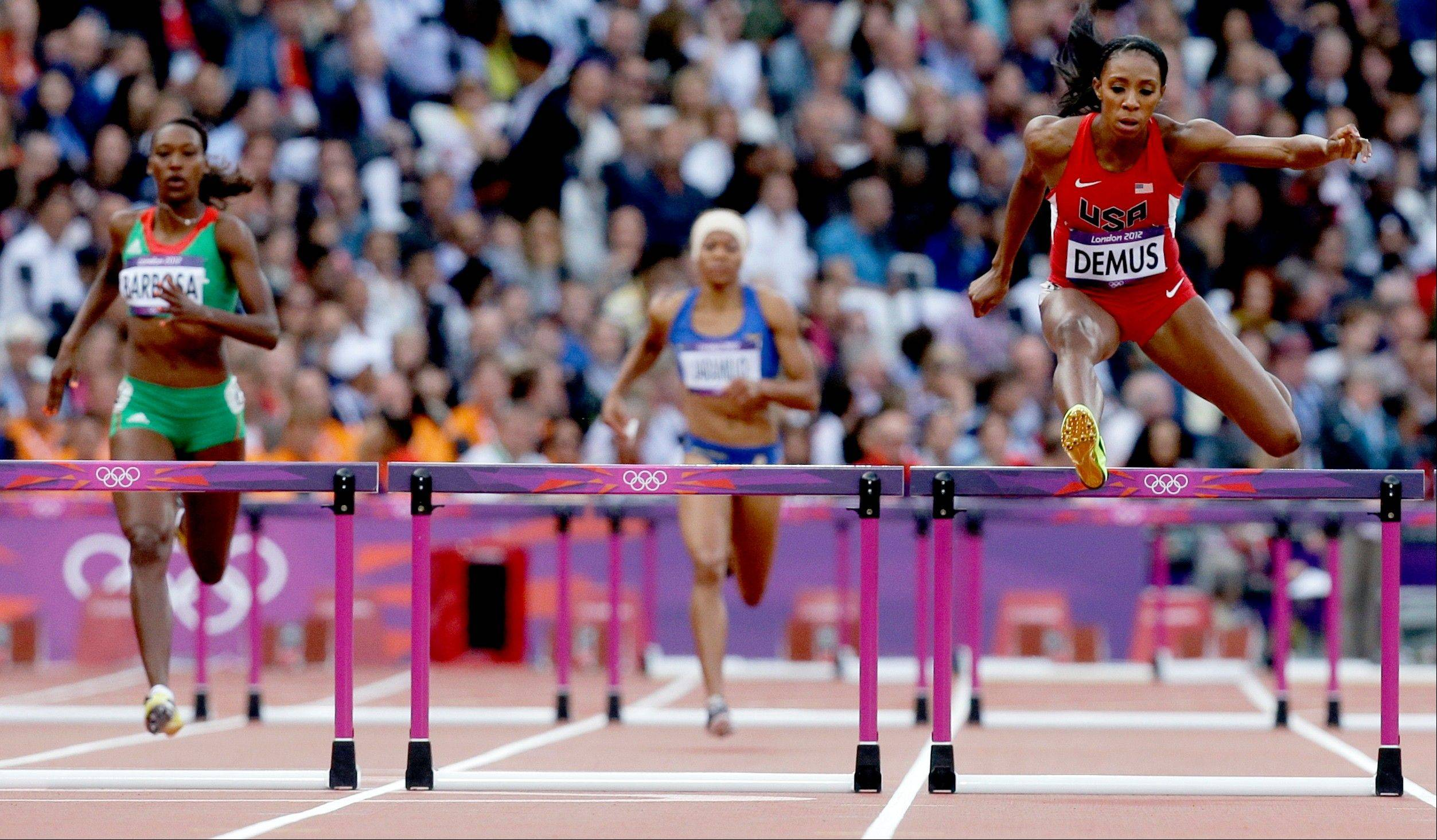 United States' Lashinda Demus right, jumps in a women's 400-meter hurdles heat during the athletics in the Olympic Stadium at the 2012 Summer Olympics, London, Sunday, Aug. 5, 2012.
