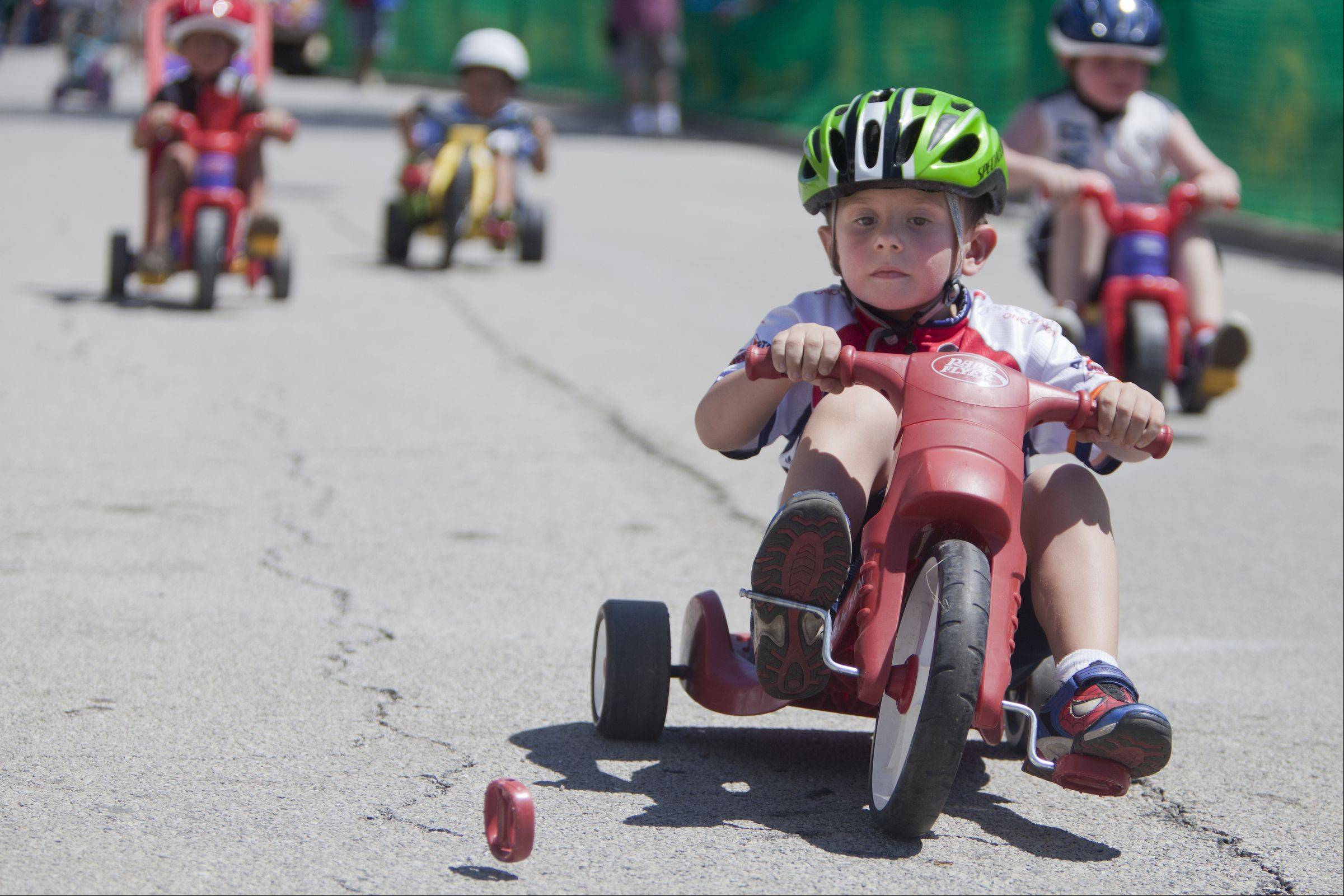 "Five-year-old Matthew Curin of Lake Zurich finishes the Shimano ""big wheels"" bike race without his right pedal during the third day of the Tour of Elk Grove."