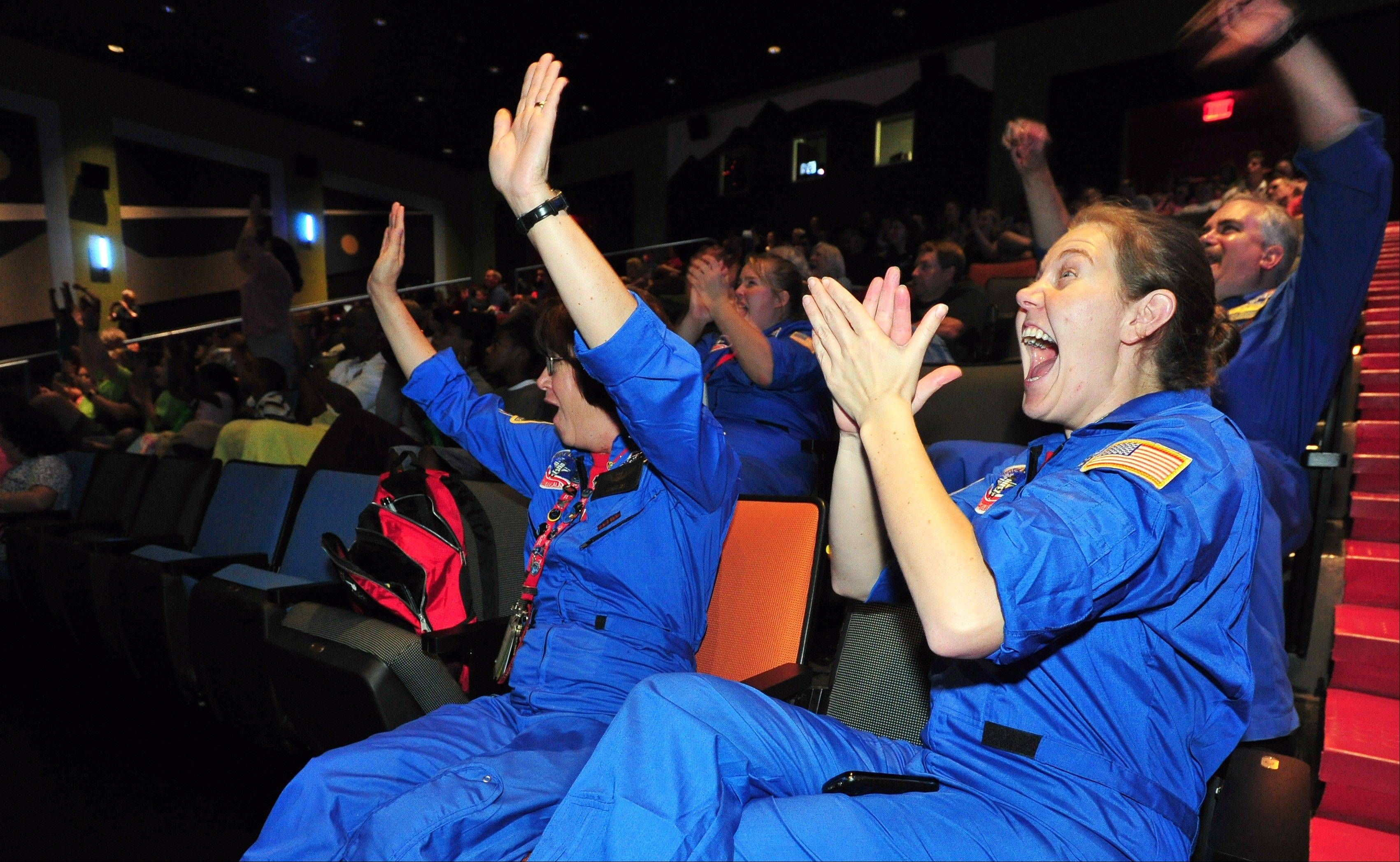 Shannon Lampton, and Charlene Pittman, both educators with the U.S. Space and Rocket Center, cheer as they watch NASA's Mars Curiosity rover land on Mars during a special viewing event at the U.S. Space and Rocket Center Monday, Aug. 6, 2012 in Huntsville, Ala.