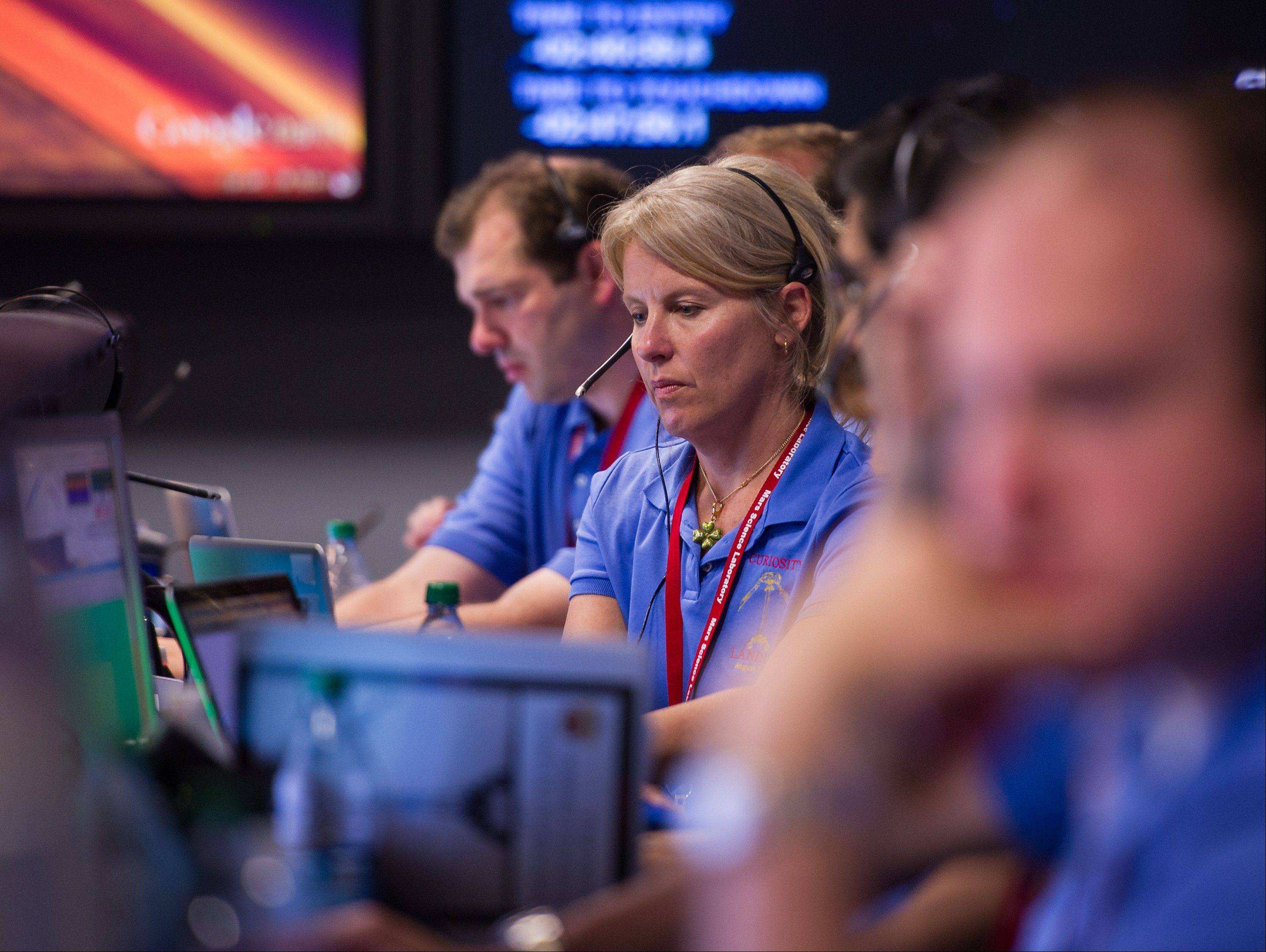 Members of the Mars Science Laboratory (MSL) team work in the MSL Mission Support Area Sunday at the Jet Propulsion Laboratory hours ahead of the planned landing of the Curiosity rover on Mars.