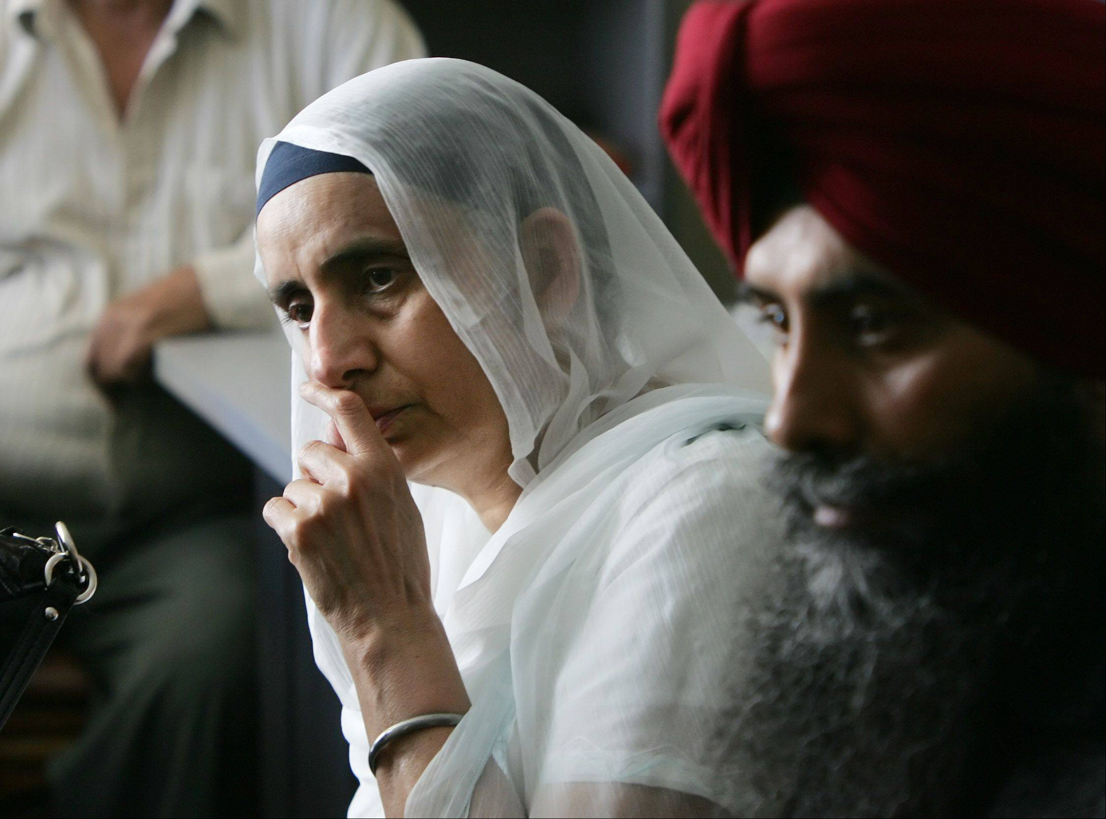 President Sukhdev K. Ghuman and other Sikh members of the Gurudawara Sikh Religious Society in Palatine watch news of the shooting at a Sikh temple Sunday near Milwaukee.