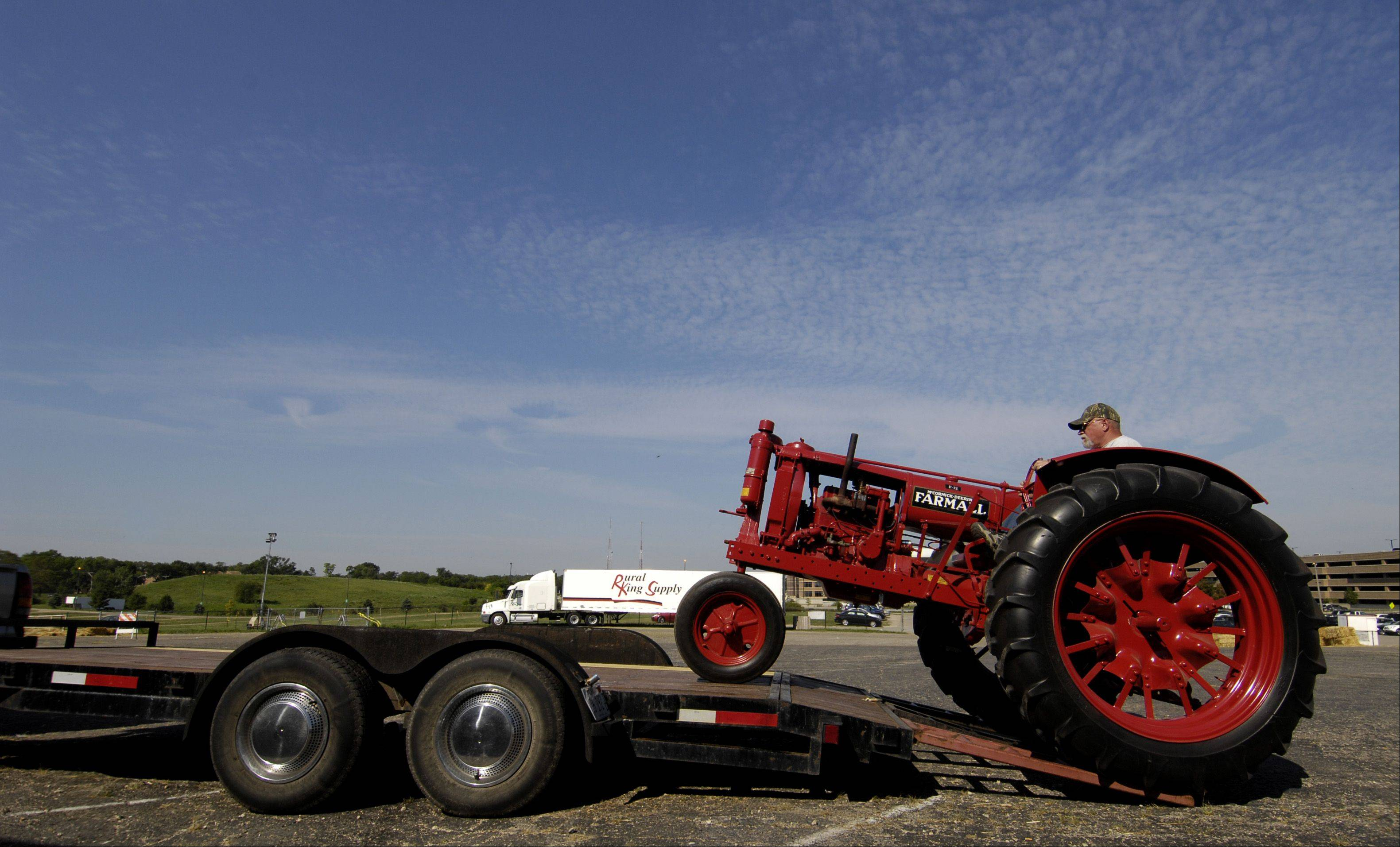 Steve Hageman of Yorkville drives a 1937 Farmall F-12 tractor onto a flatbed trailer as he and his father Wilbert pack up their antique tractors after the 2012 DuPage County Fair, Monday. The Hageman family used to farm in Naperville.