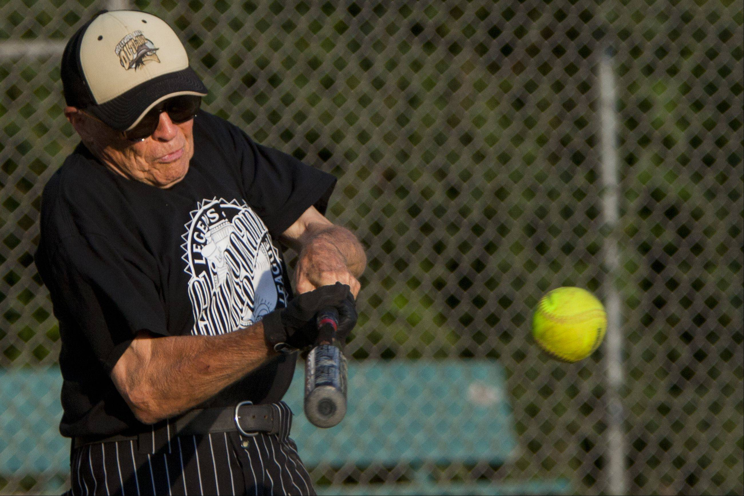 82-year-old Ken Black the oldest member of the Chicagoland Legends Softball League hits a line-drive back to pitcher.