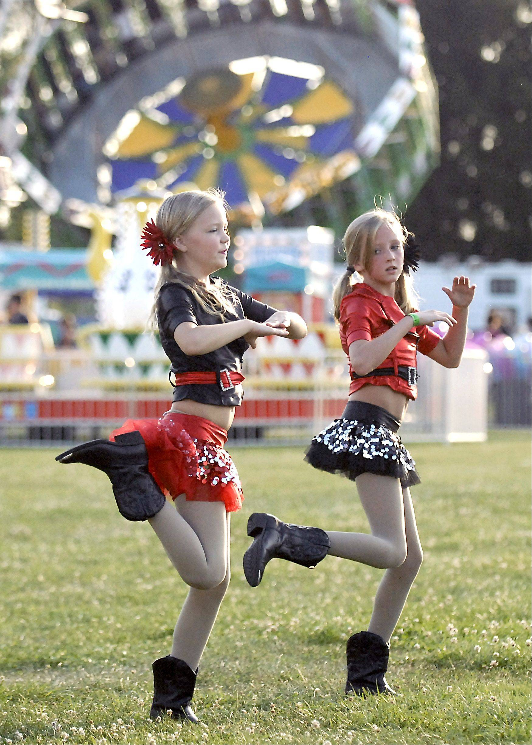 Olivia Bruneman, left, of Kingston and Emma Hockey of Maple Park, both 10, rehearse their dance number backstage at Hampshire's Coon Creek Country Days in Bruce Ream Park on Thursday, August 2. The girls are dance with the Northern Illinois Dance Center, which is located in Hampshire. Over 25 dance students performed 11 acts as the opening entertainment for the festival.