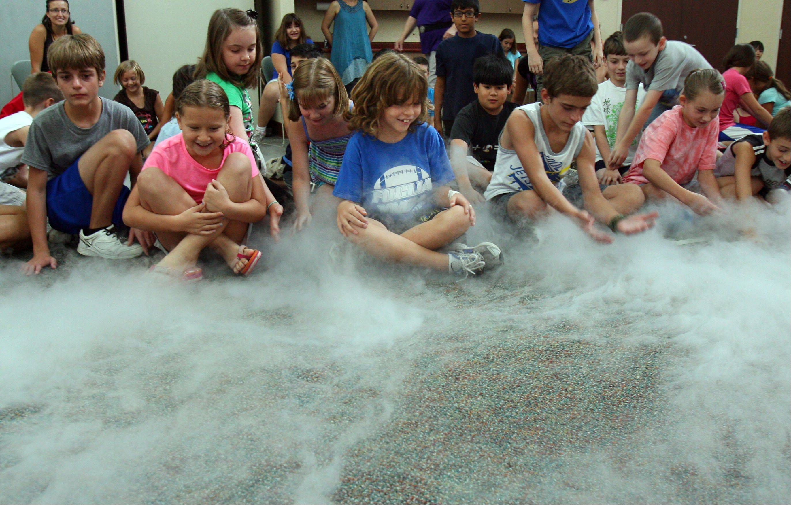 "Kids react as steam from liquid nitrogen covers the carpet in front of them during a show by Bill Bosworth of The Science Alliance called ""Close Encounters of a Chemical Kind"" at Lake Villa District Library Thursday in Lake Villa."