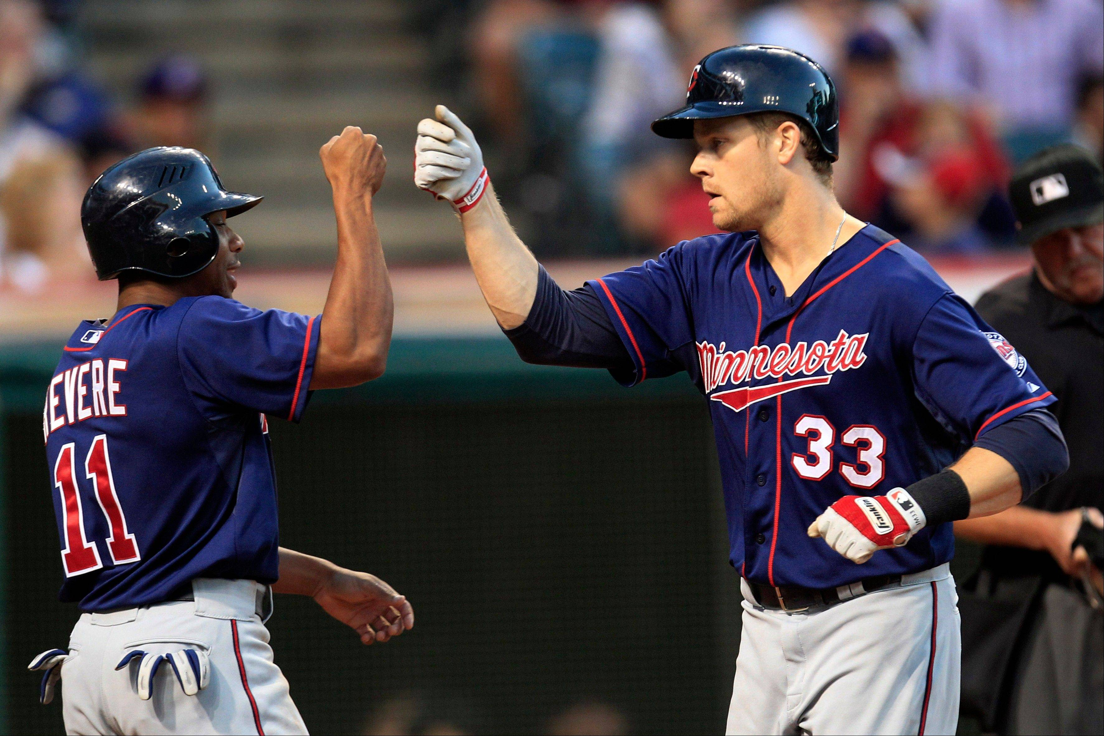 The Twins' Ben Revere, left, congratulates Justin Morneau on his two-run home run off Indians pitcher Josh Tomlin in the fourth inning Monday in Cleveland.