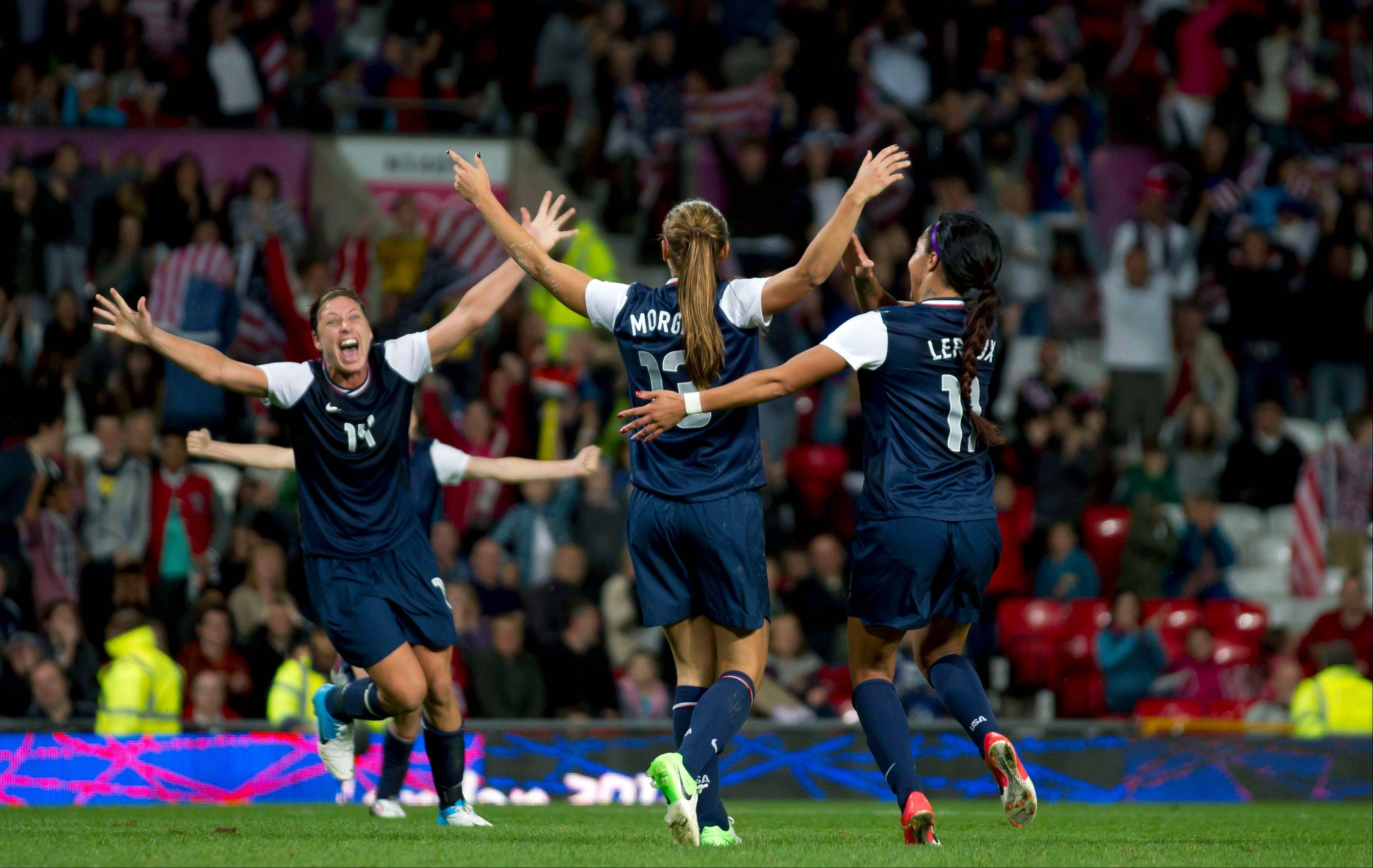 United States' Alex Morgan, center, celebrates with teammates including Abby Wambach, left, and Sydney Leroux after the winning goal was scored past Canada's goalkeeper Erin Mcleod during their semifinal women's soccer match Monday at the 2012 London Summer Olympics, at Old Trafford Stadium in Manchester, England.