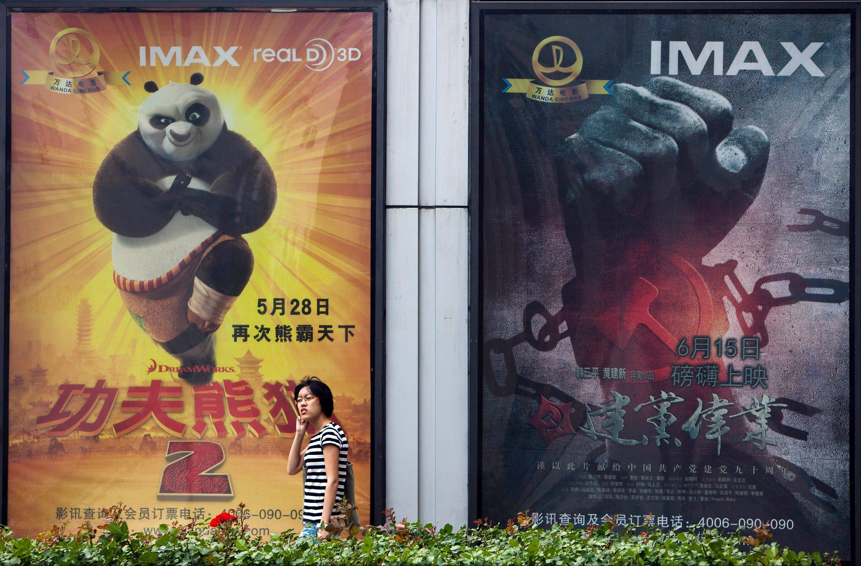 "A woman walks past movie posters of Hollywood movies ""Kung Fu Panda 2,"" left, and China's propaganda film ""Beginning of the Great Revival"" on display side by side outside a cinema in Beijing."