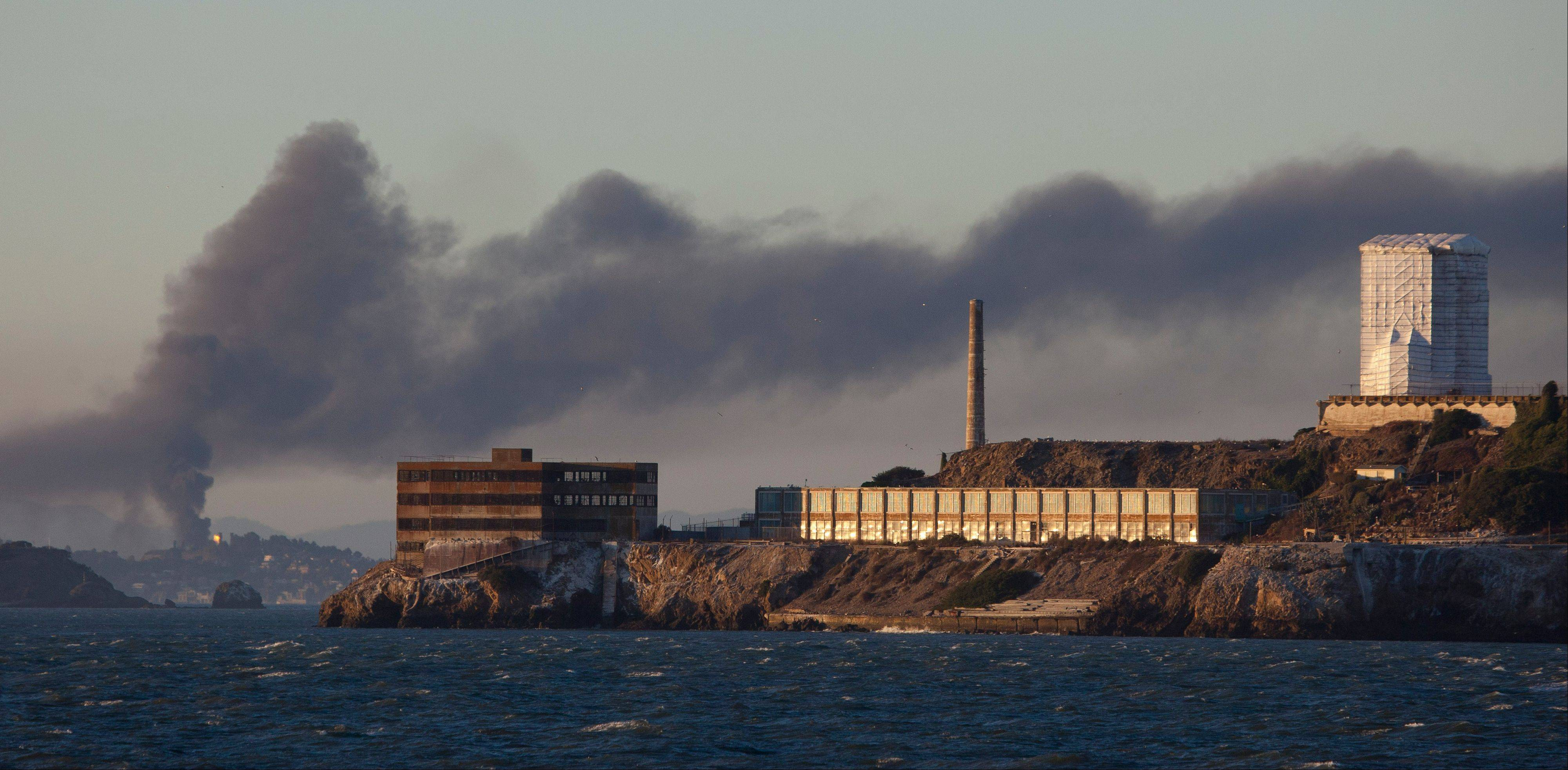 Smoke pours from a fire at the Chevron Richmond Refinery, seen behind Alcatraz Island in San Francisco.
