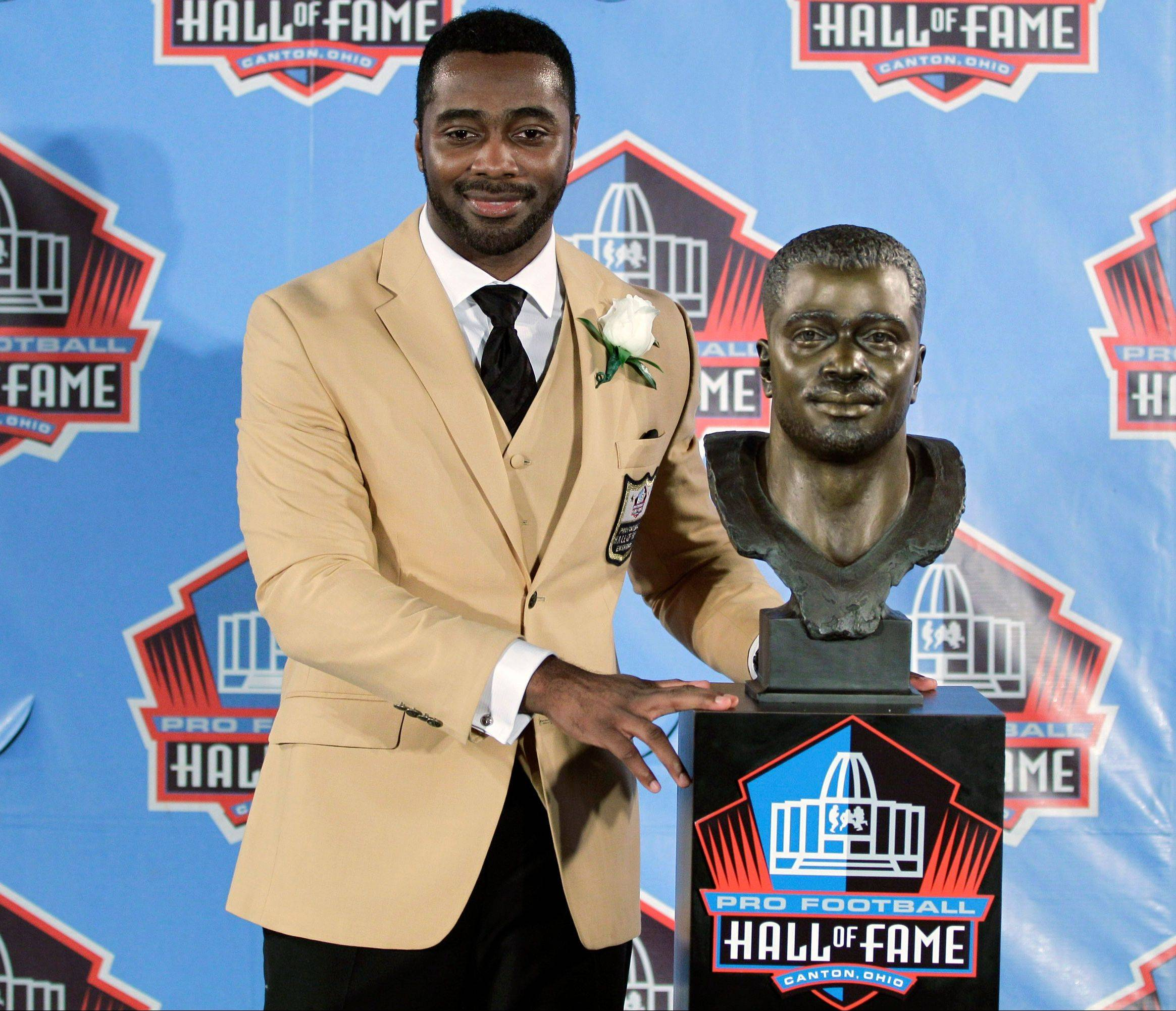 Curtis Martin poses with a bust of himself during induction ceremonies Saturday at the Pro Football Hall of Fame.