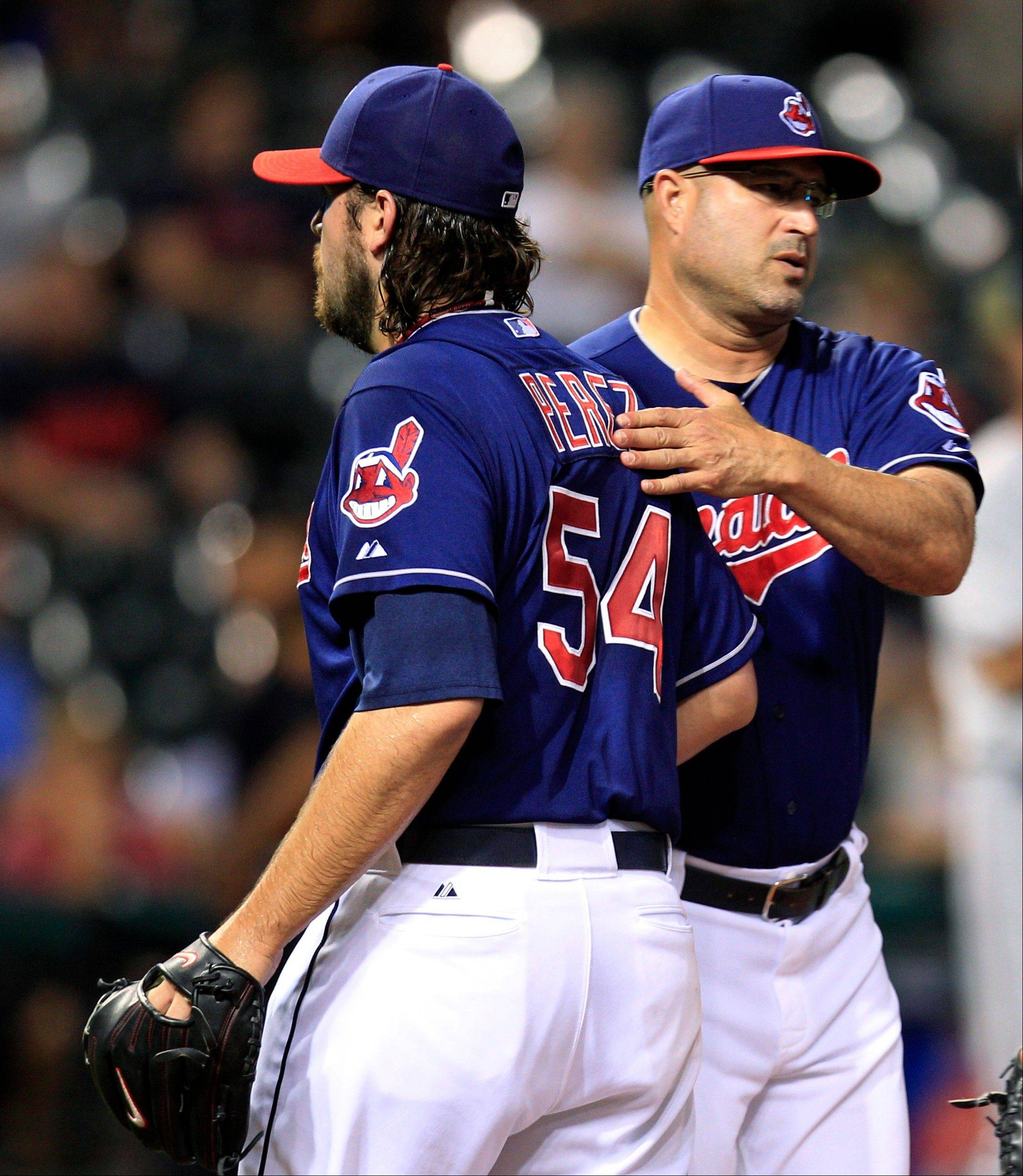 Manager Manny Acta pats Chris Perez on the back after the Indians reliever blew a ninth-inning lead Tuesday against the Twins in Cleveland.