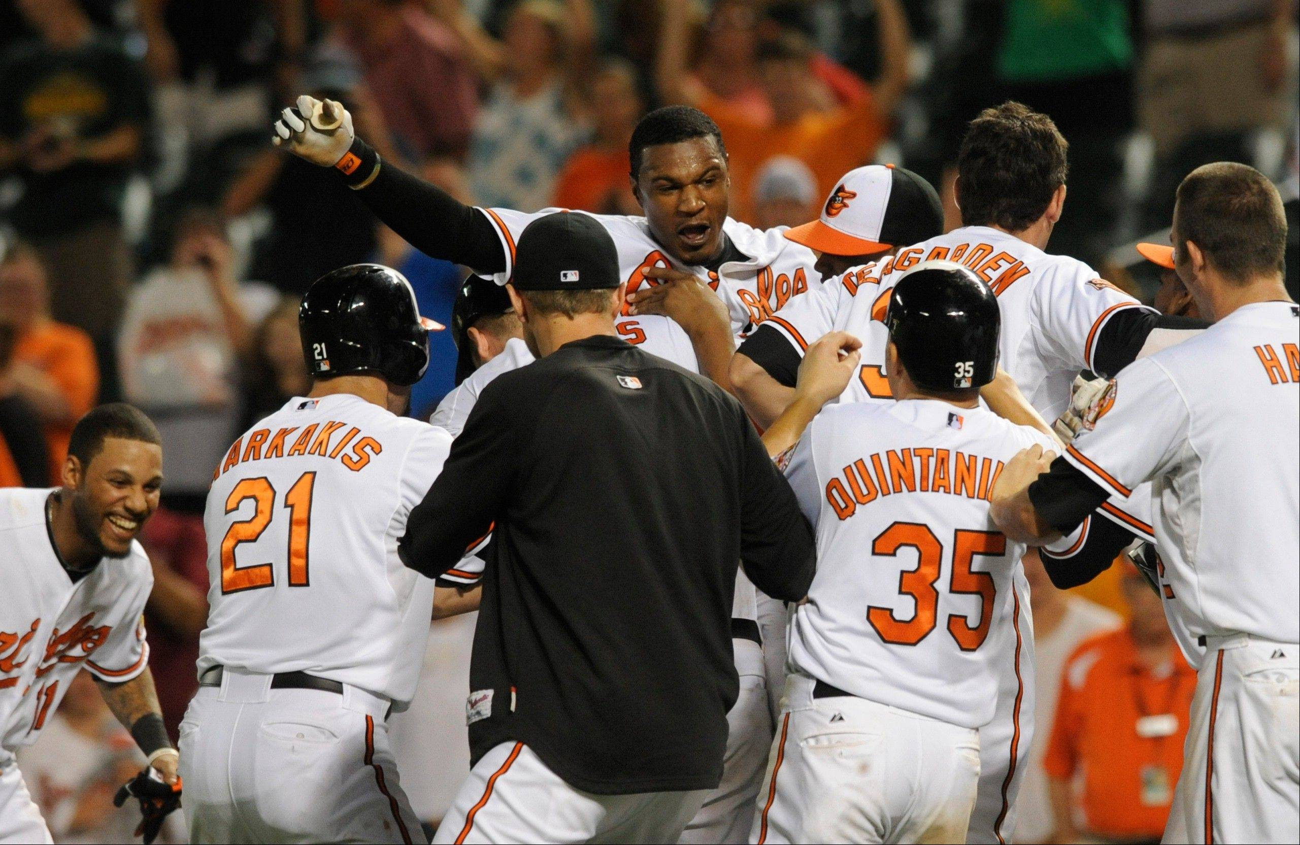 Baltimore players swarm Adam Jones after he drove in the winning run against the Seattle Mariners in the 14th inning Tuesday at home.