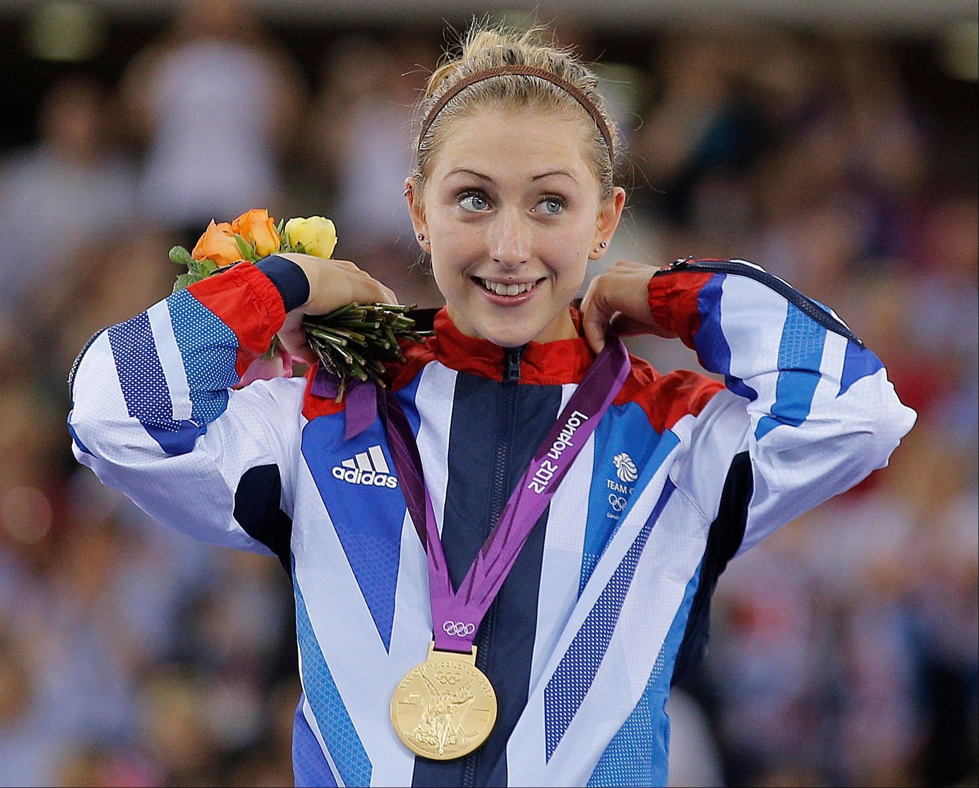 Gold medalist Laura Trott of Britain adjusts her gold medal for the track cycling women's omnium event Tuesday during the 2012 Summer Olympics in London. Britain has now won more Olympic gold medals than at any Summer Games in 104 years.