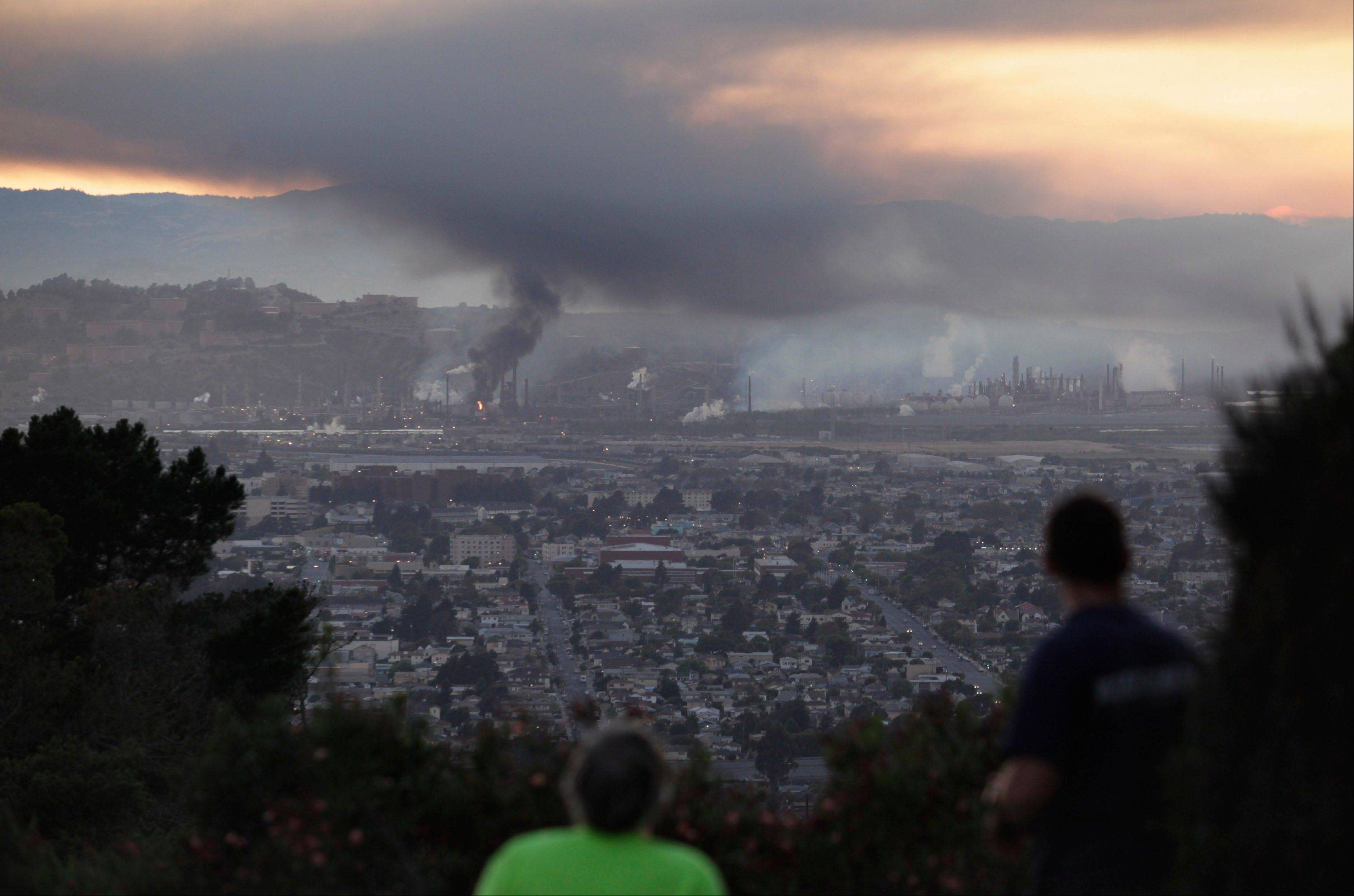 People watch smoke rise from the Chevron refinery in Richmond, Calif., from a vantage point in the El Cerrito hills Monday. Officials told residents of two Northern California cities to shelter-in-place as a fire at a Chevron refinery in Richmond releases plumes of black smoke.